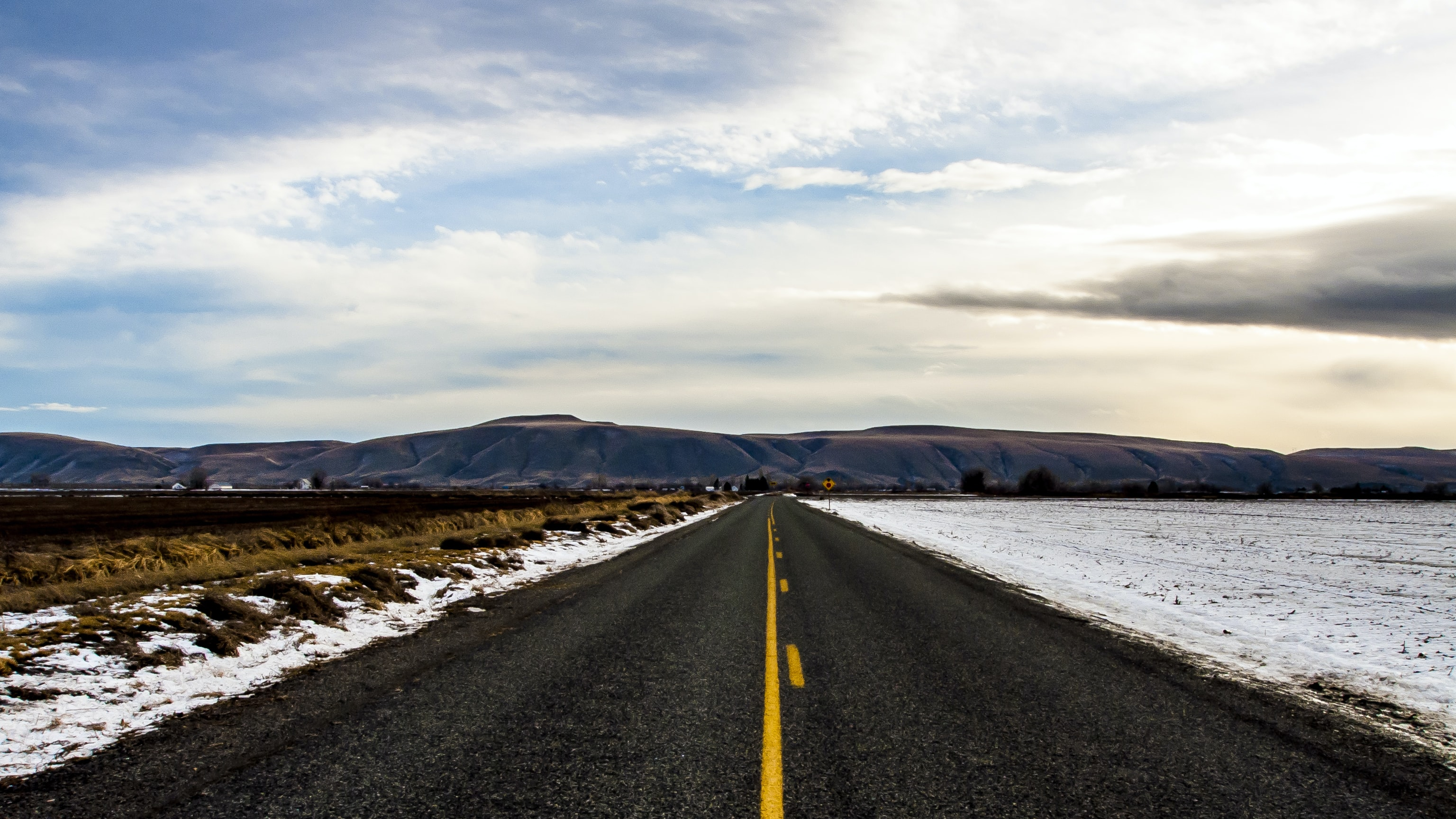 A blacktop road approaches blue mountains and sits between flatland lightly covered in snow