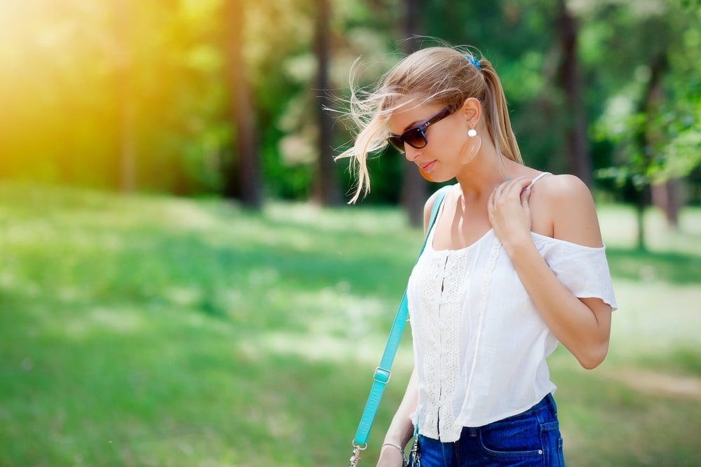 woman in white spaghetti strap top walking near trees