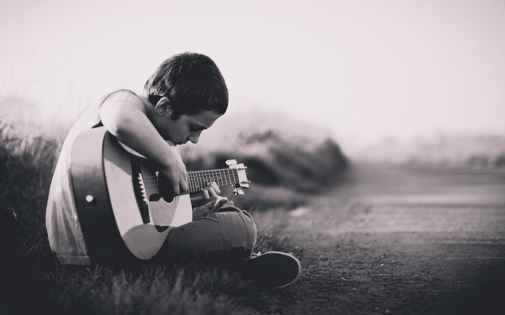 grayscaled photo of boy playing guitar