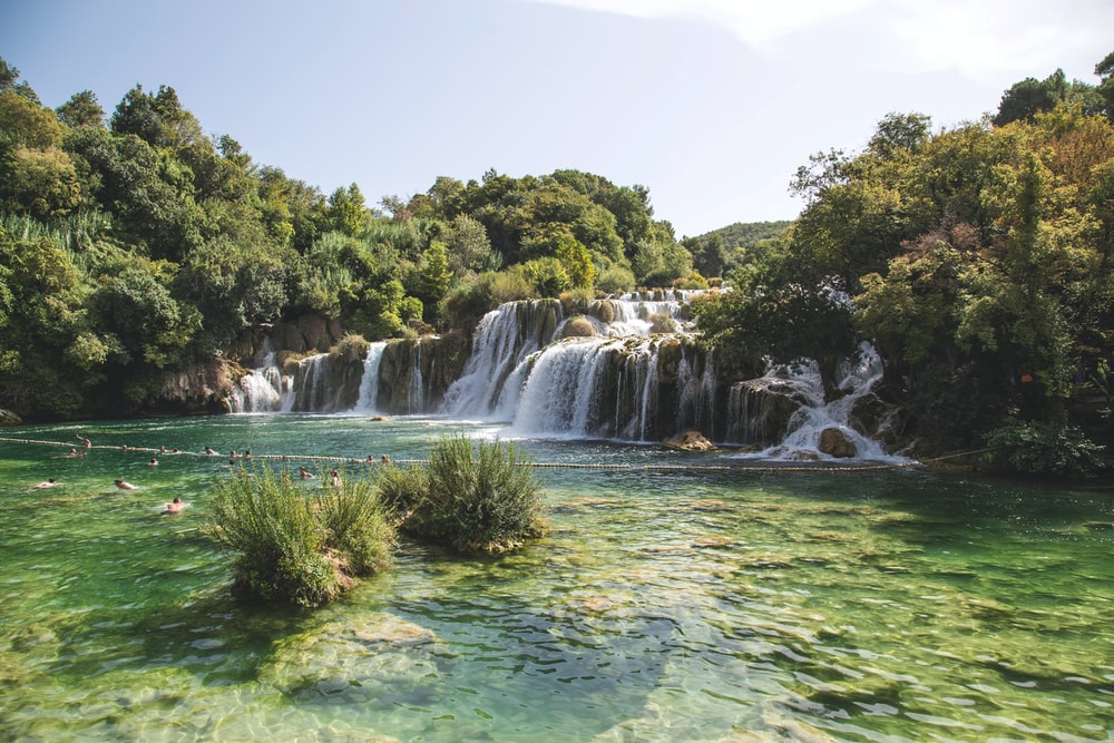 landscape photo of waterfalls flowing into river during daytime