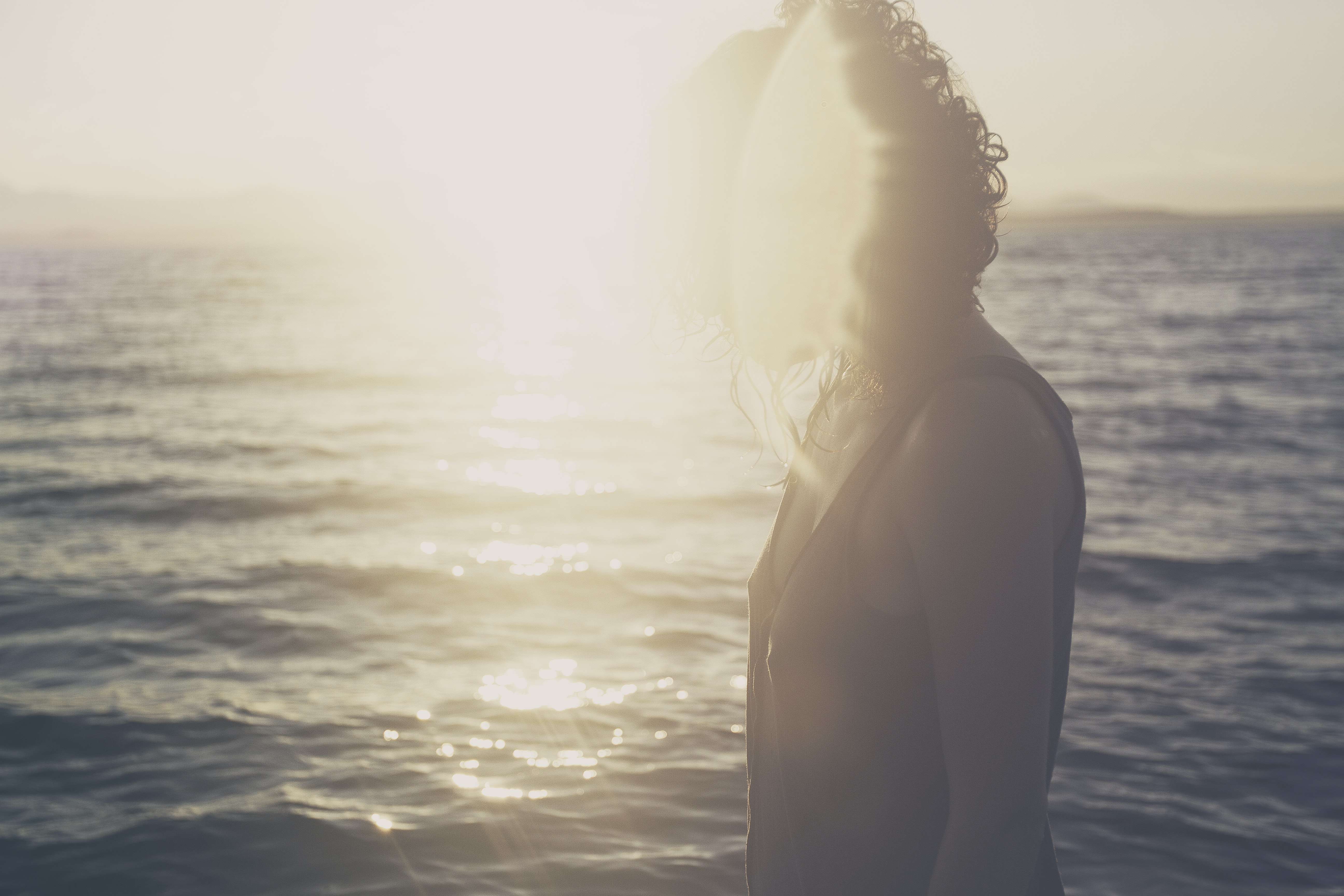 woman standing on body of water under sunset