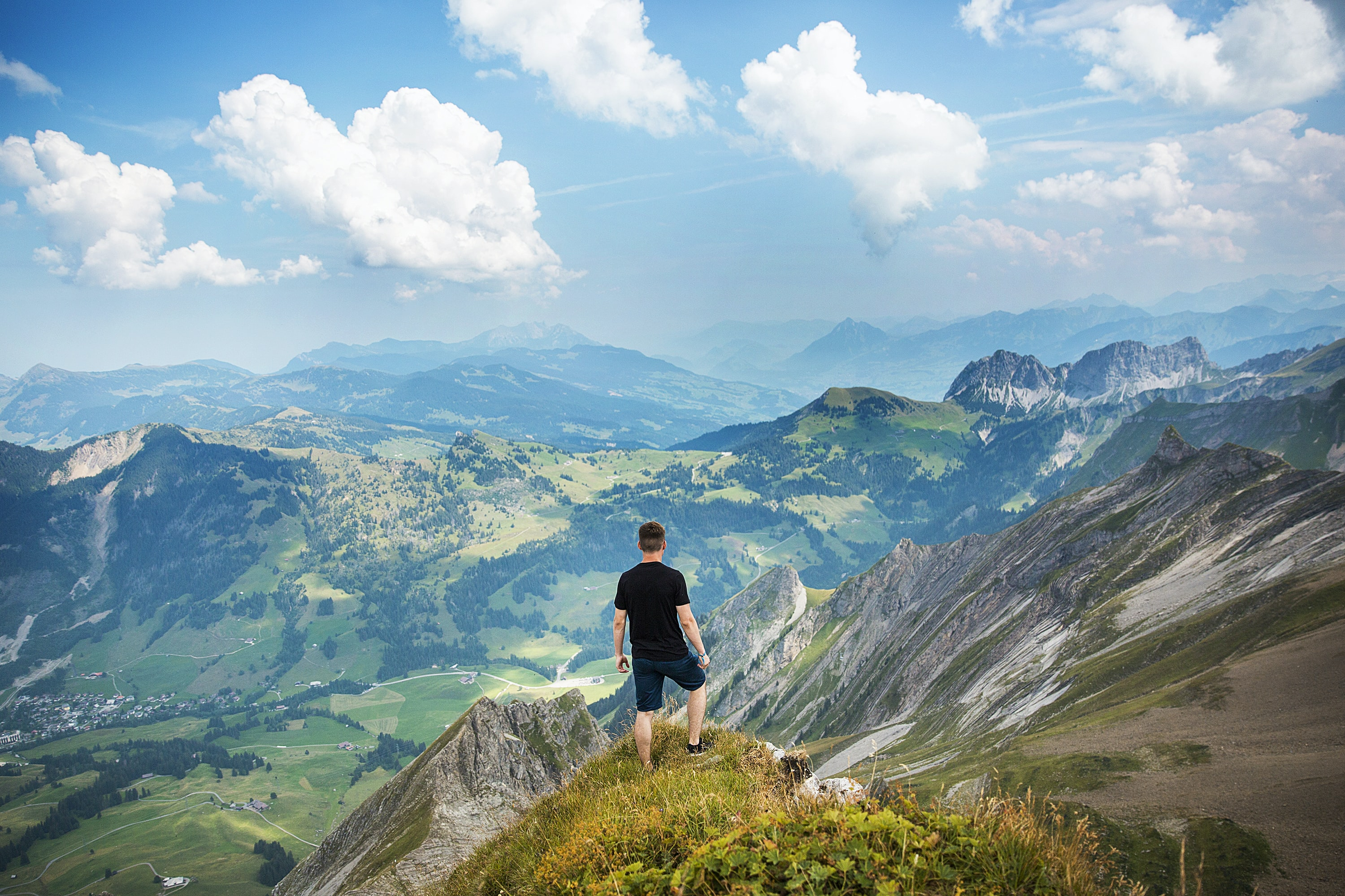A male hiker standing on a grassy ledge overlooking a rural mountain valley