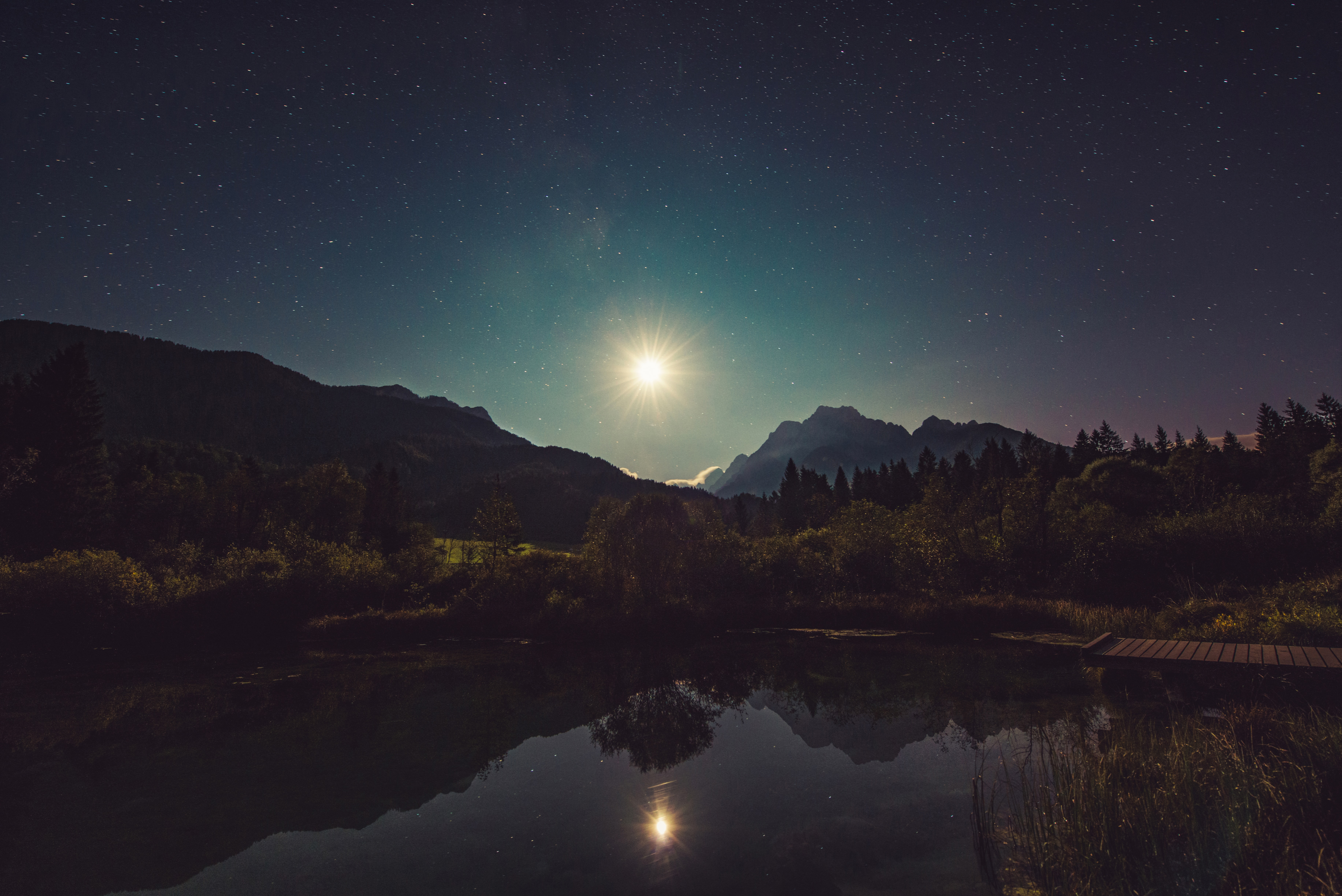 The mountains, forest, and lake lit up by the moon and starry sky in Zelenci