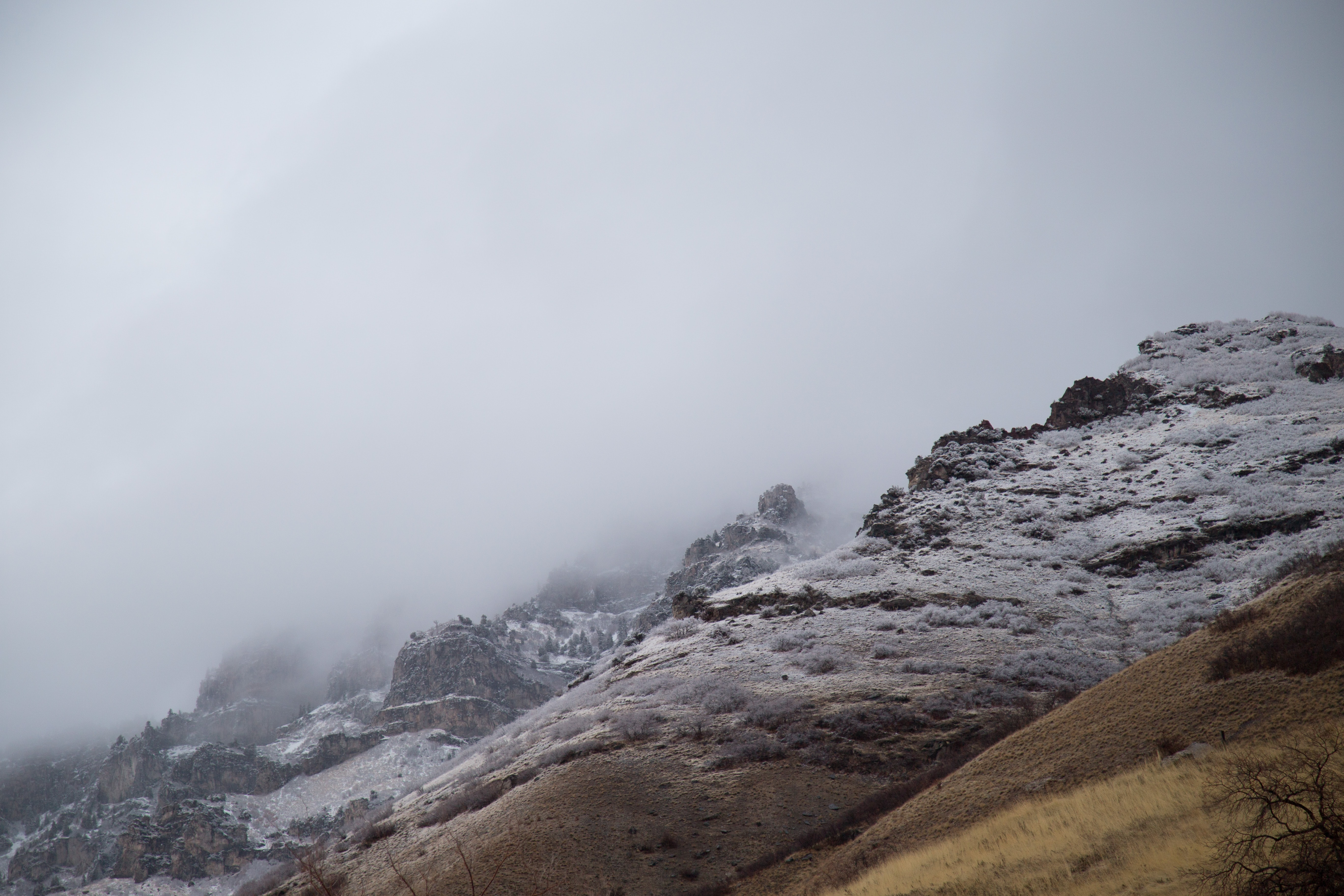 A landscape with mist rolling down mountain peaks