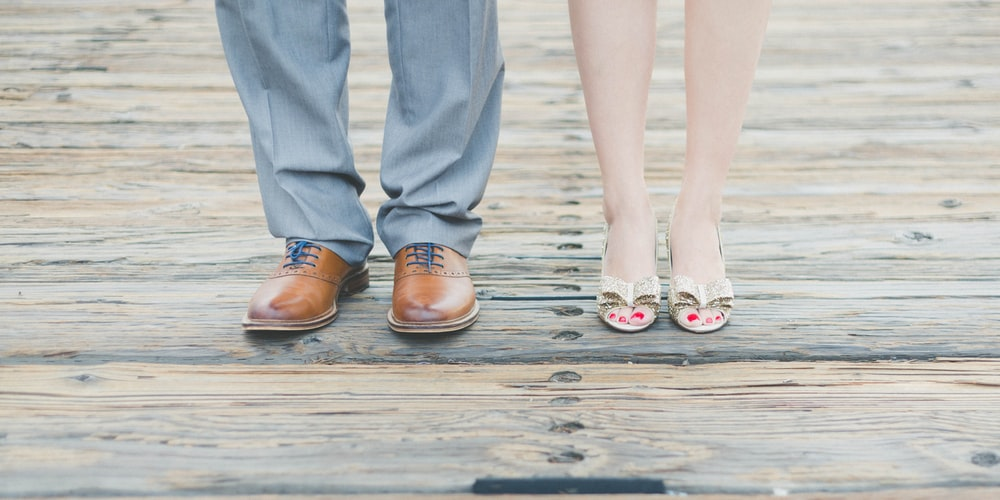 man wearing brown leather oxford shoes beside woman wearing gold open-toe sandals