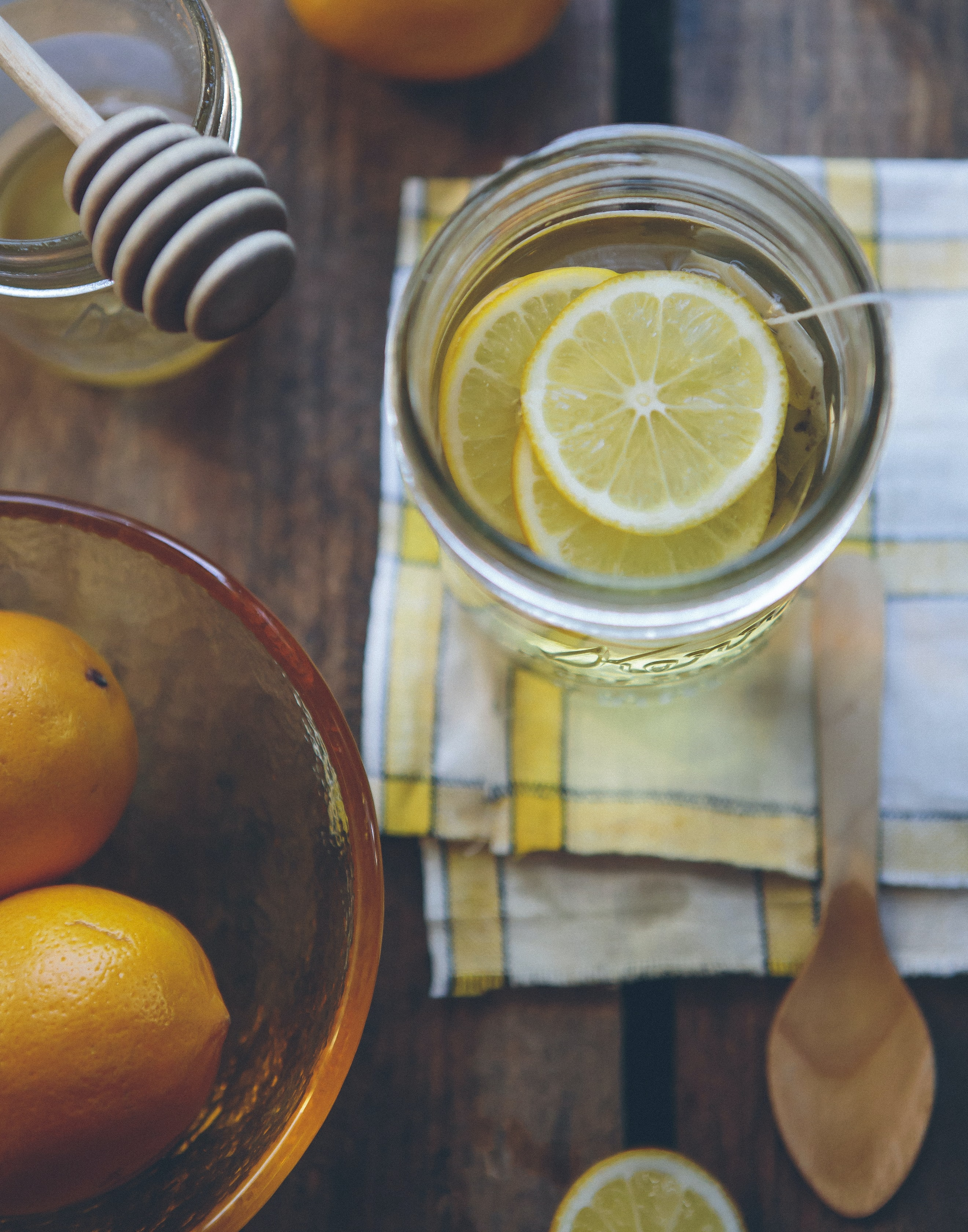 Mason jar of tea infused with lemons and honey on a kitchen table