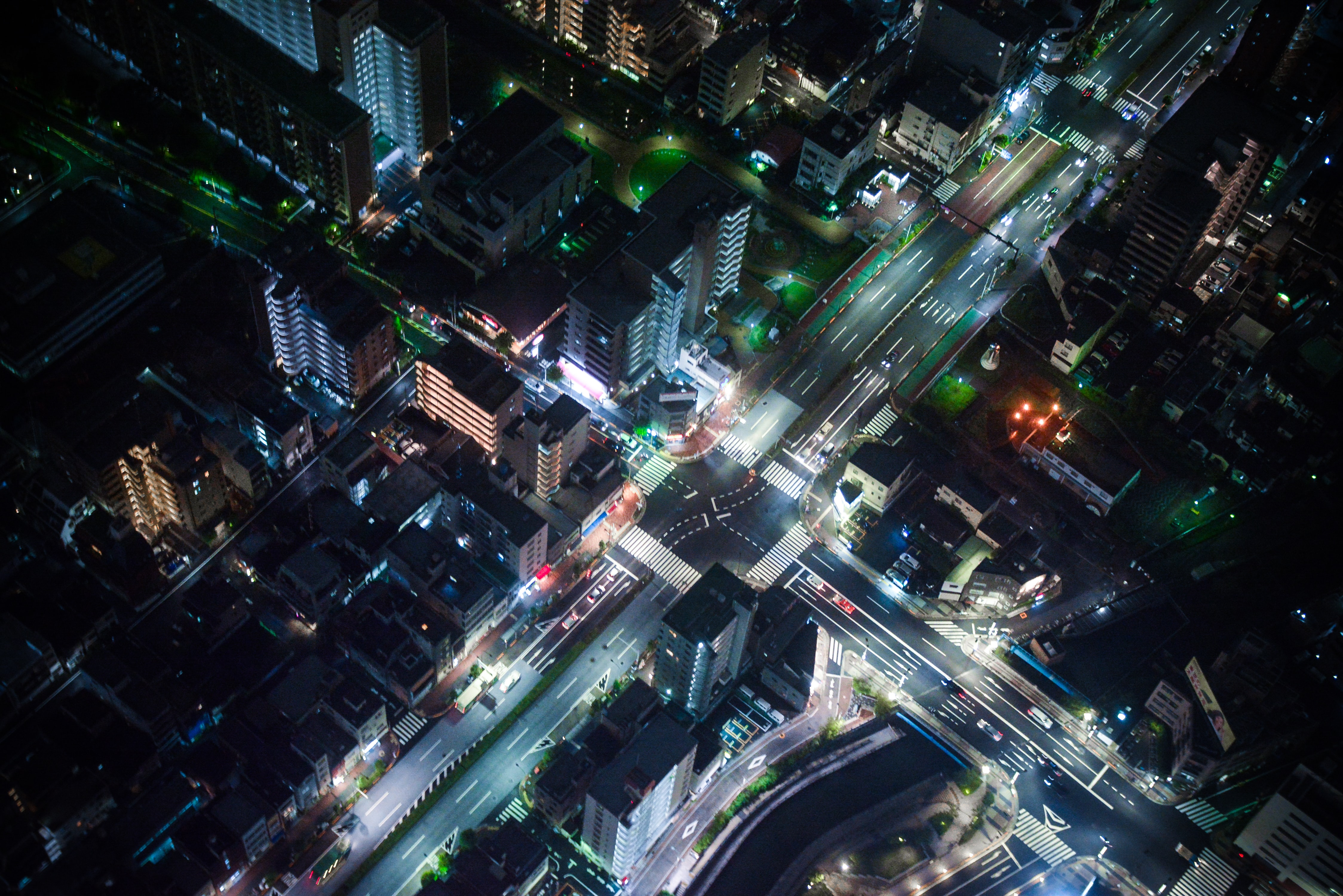 A drone shot of neon-soaked streets at night