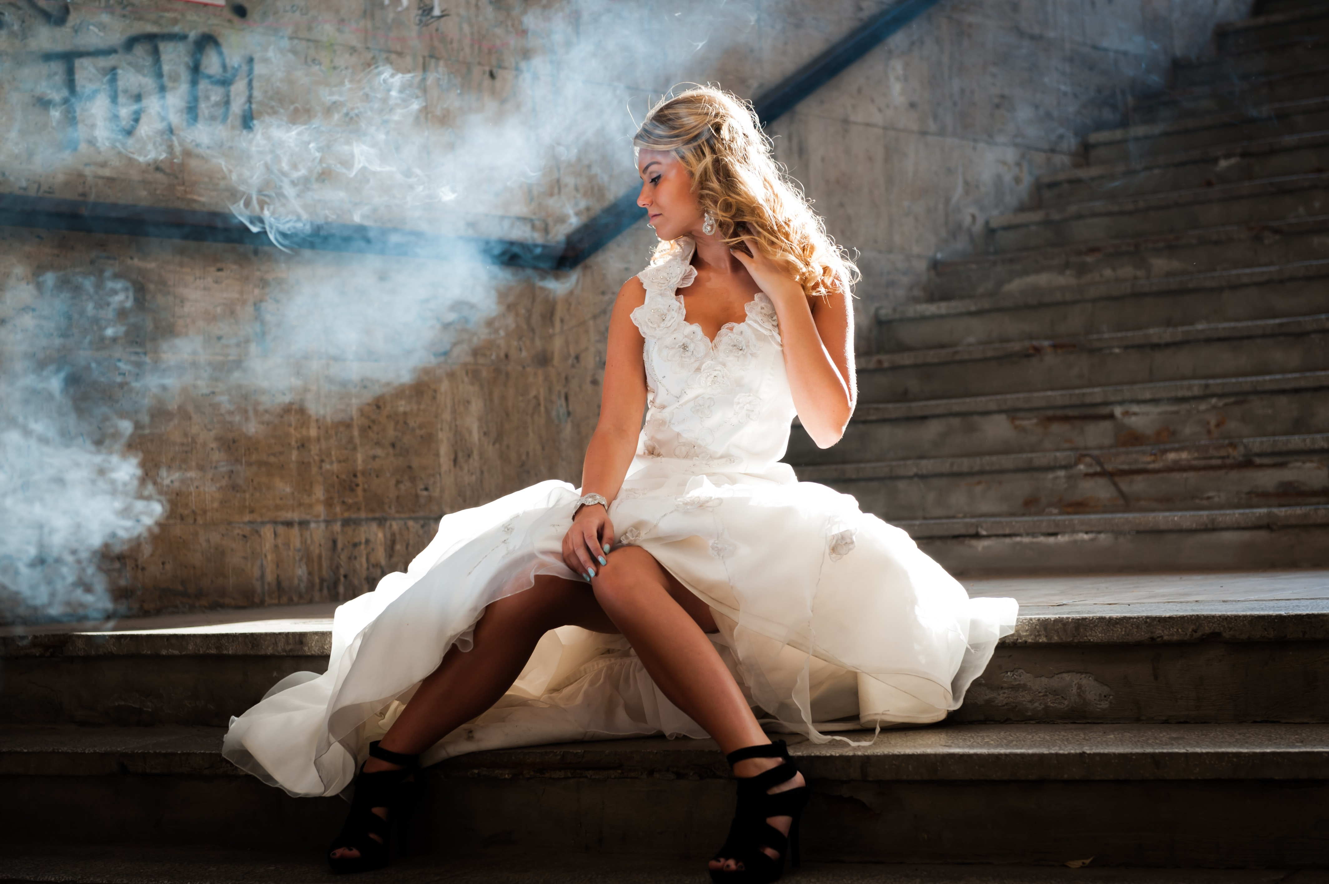 Woman in a wedding gown siting on a smoky subway staircase