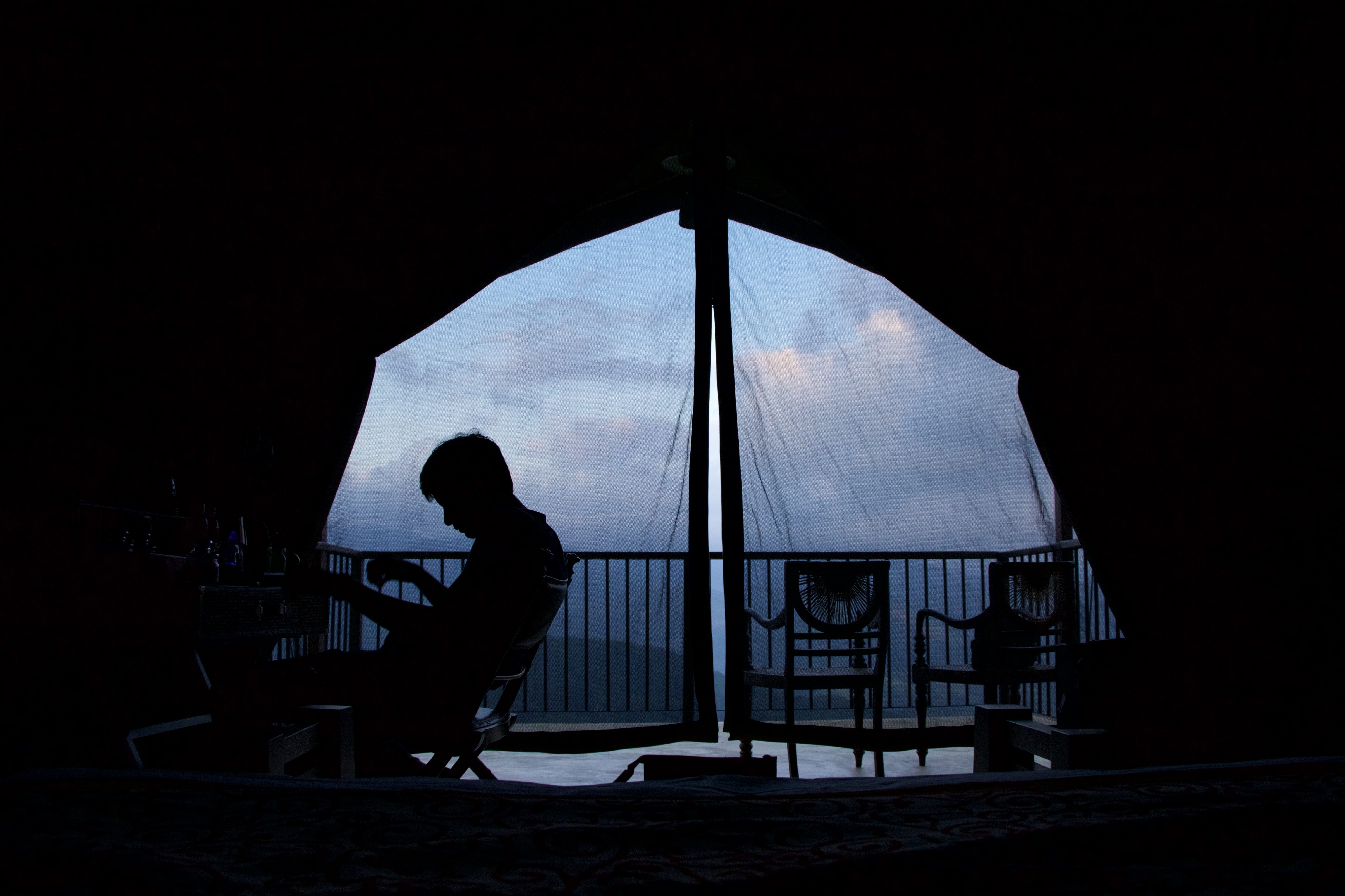 Silhouette of a person sitting on a chair in a tent at dusk