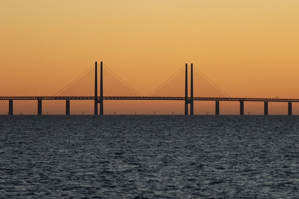 bridge during sunset with body of water