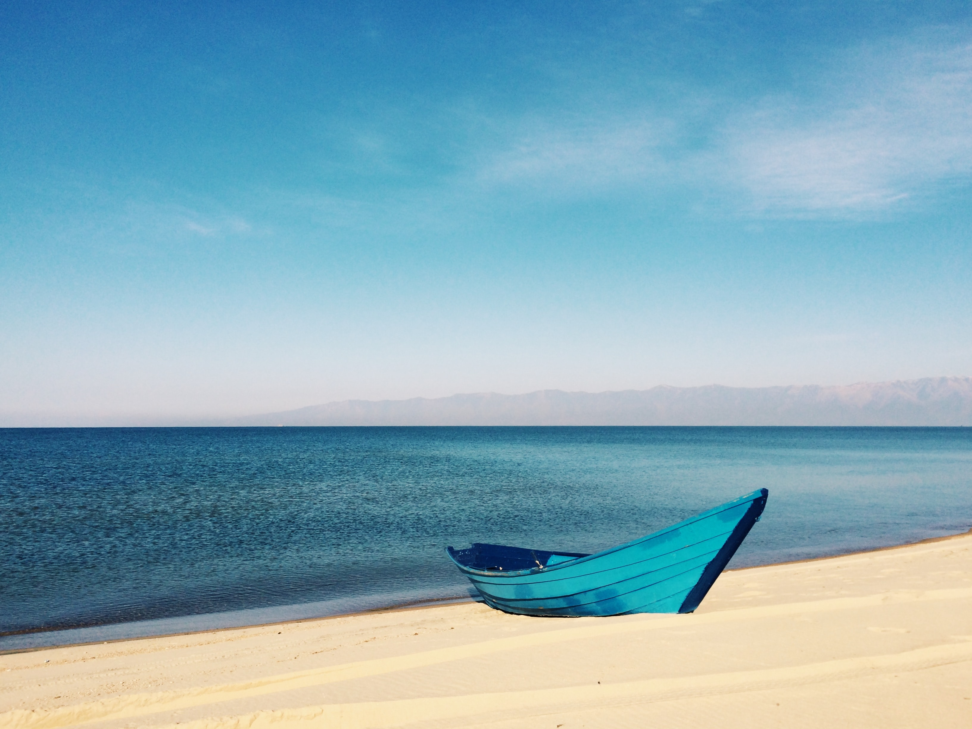 blue boat on sand near body of water during daytime