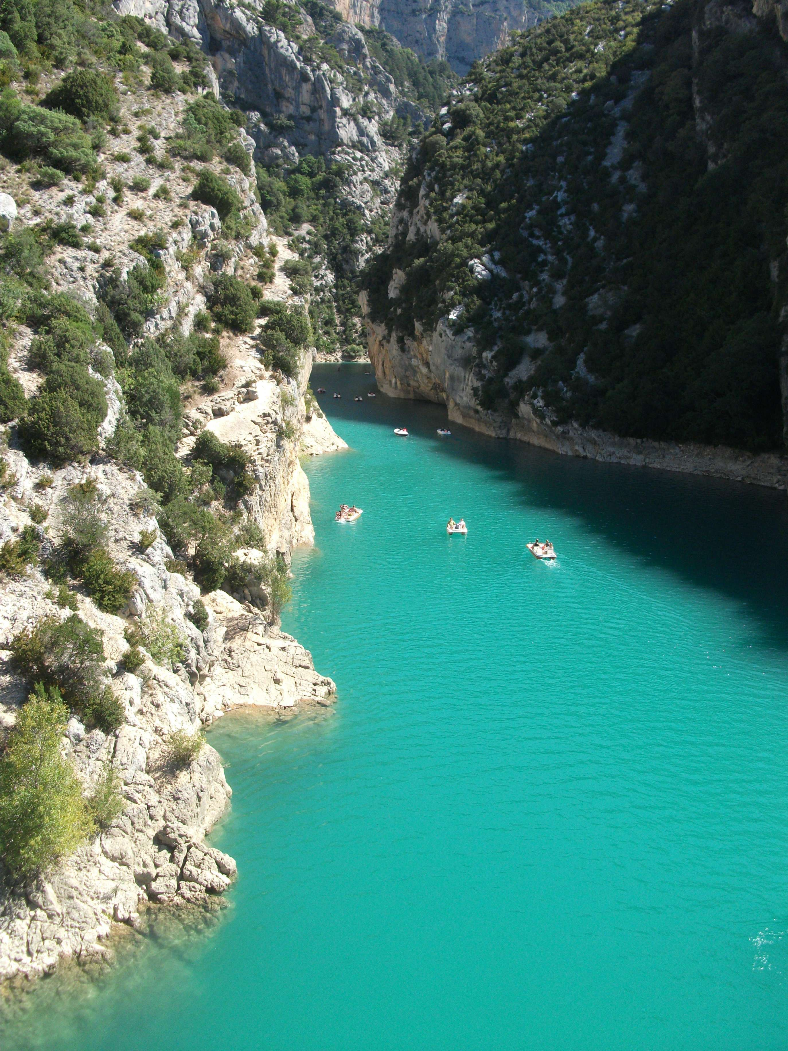 Boats on turquoise water in a white-rock canyon