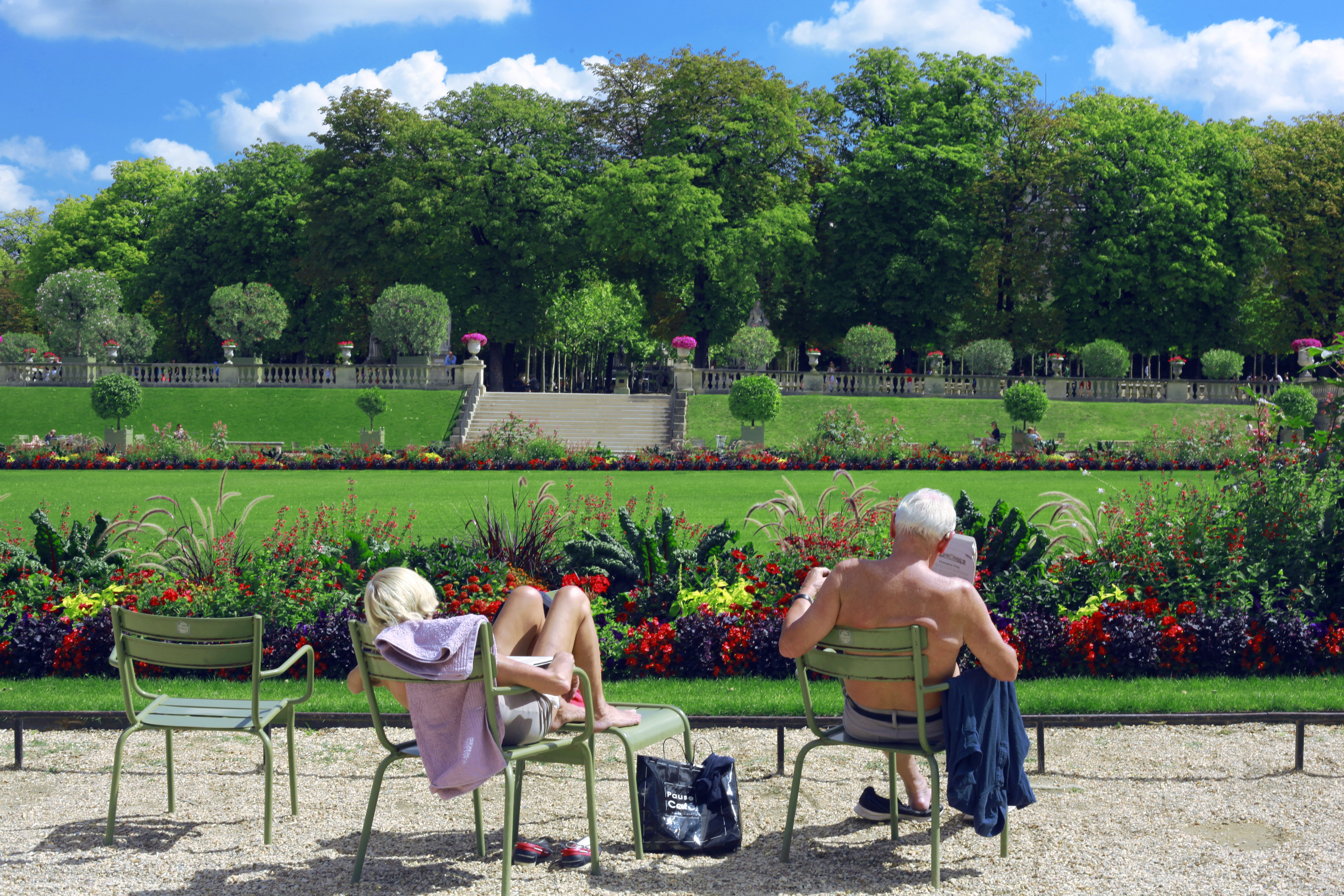 Charmant Caucasian Woman And Man Relaxing And Sunbathing In Beautiful Flowery Garden  At Le Jardin Du Luxembourg