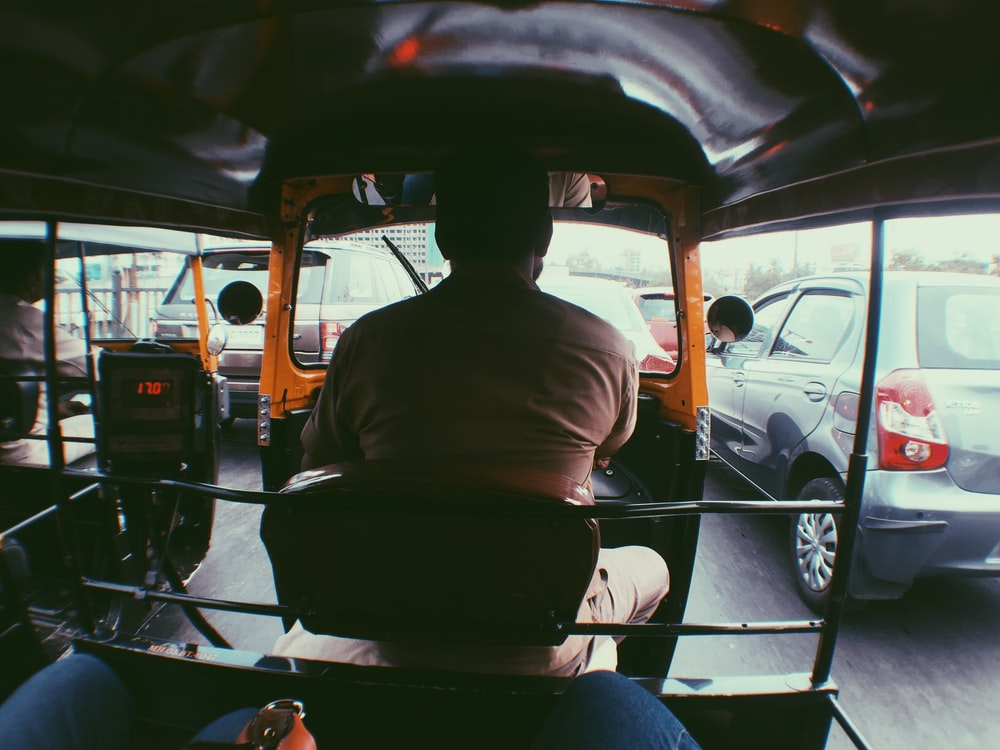 man in brown shirt driving car during daytime