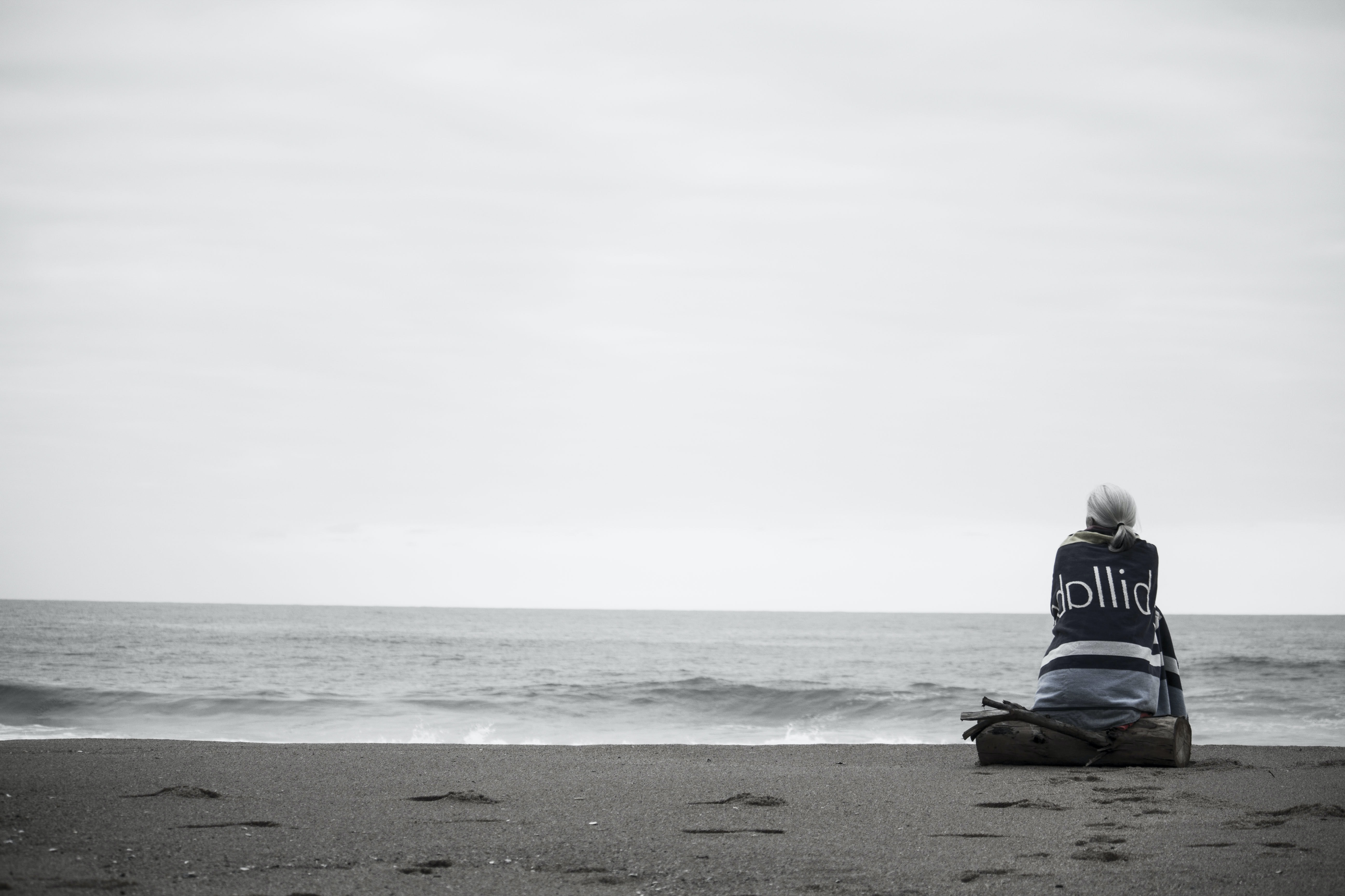 Black and white shot of a woman sitting alone in the seashore watching the still ocean