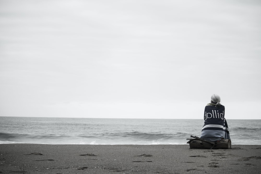 woman sitting near seashore during daytime