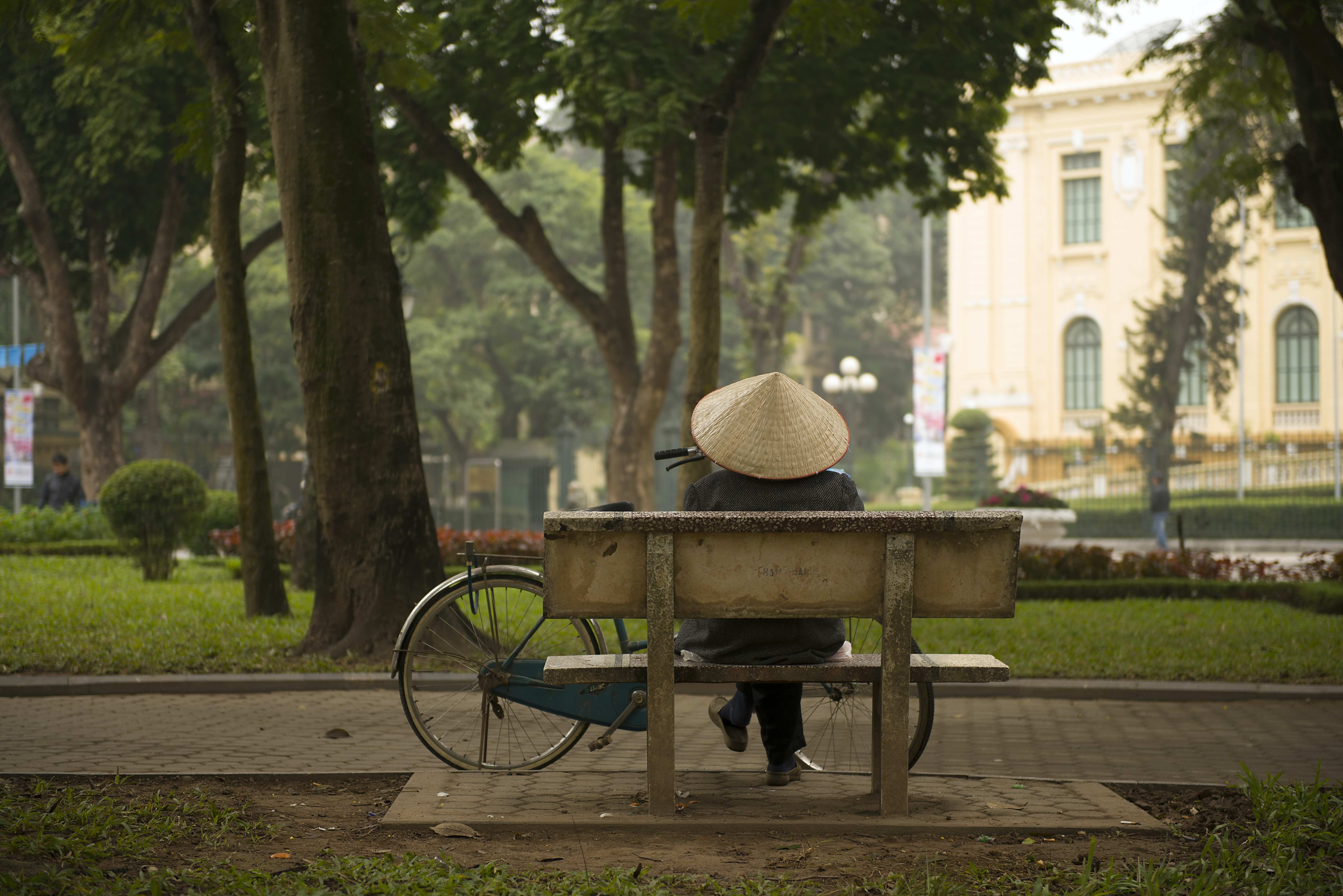 A person wearing a traditional Vietnamese hat sitting on a park bench with their bicycle nearby in Hanoi