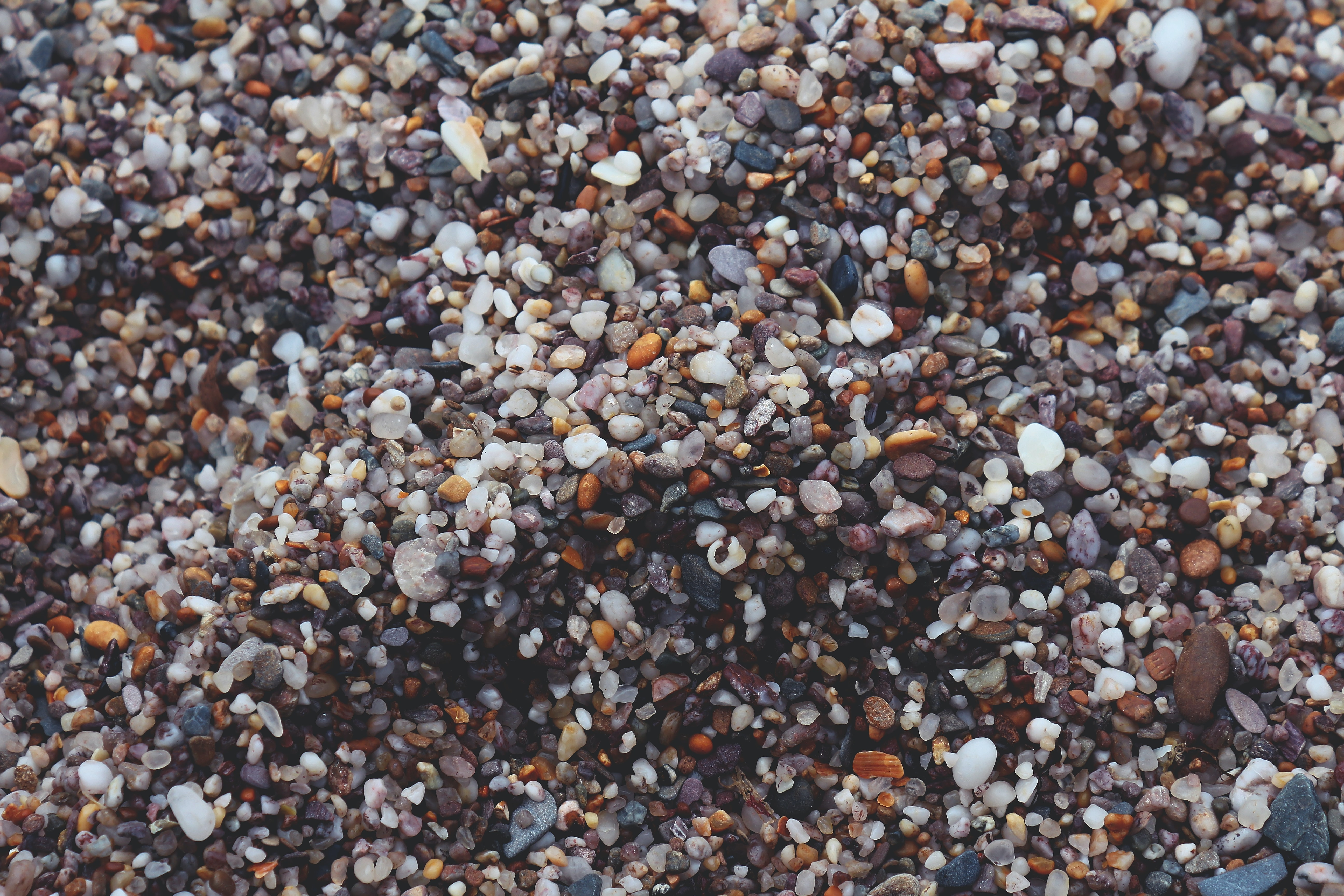 A top view of a large number of pebbles of various color, shape and size