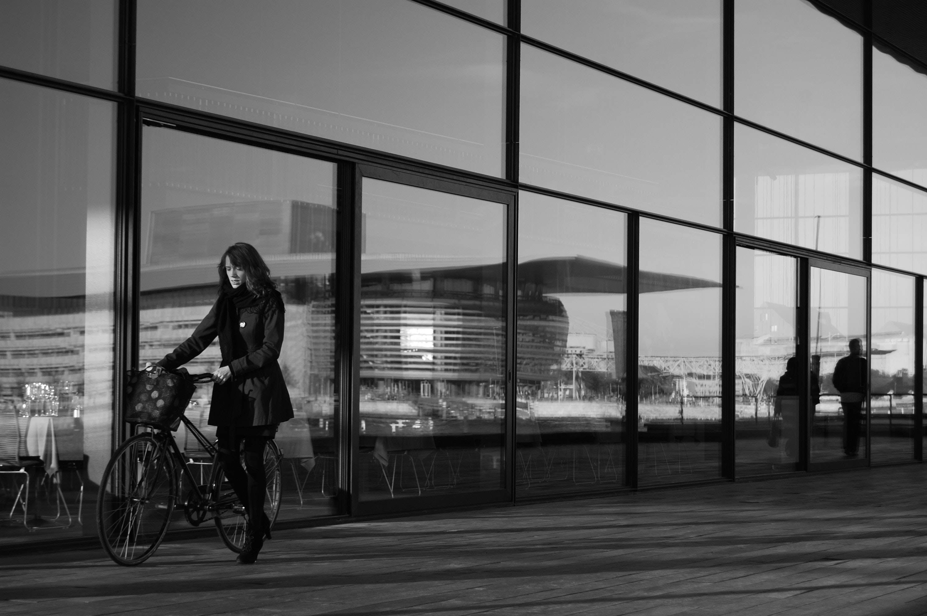 grayscale photography of woman holding bicycle