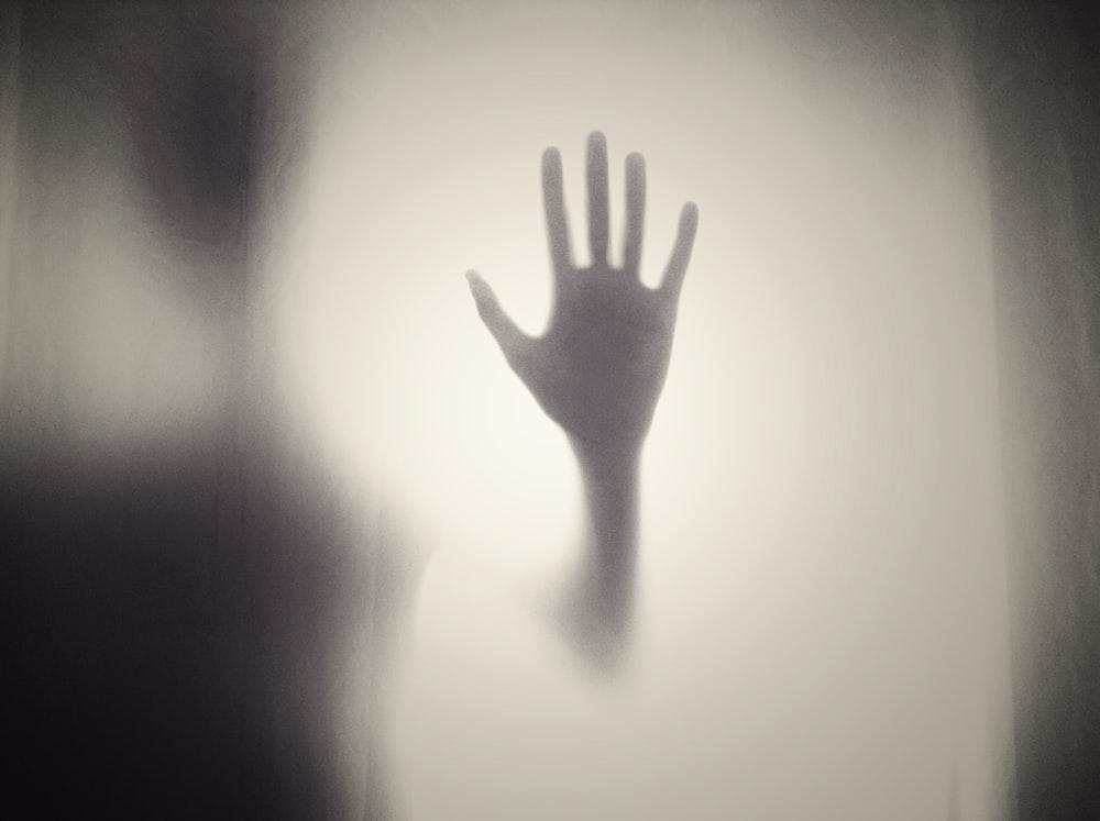 person shadow holding glass door
