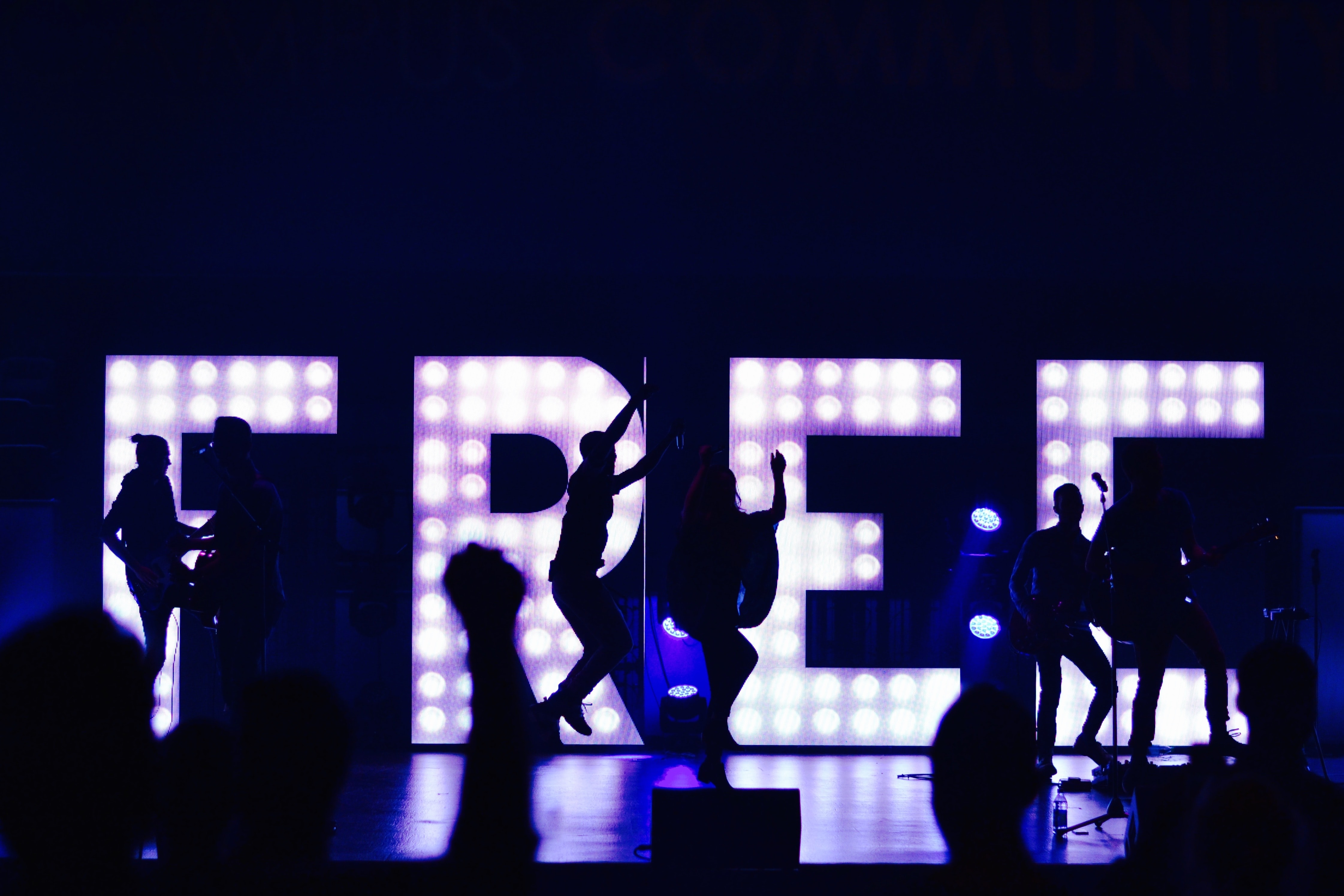 "Silhouettes of band members performing and jumping up in front of lights arranged to spell out ""free"""