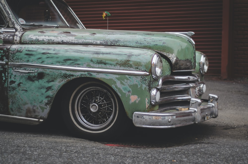 close-up photo of classic green car parked near building