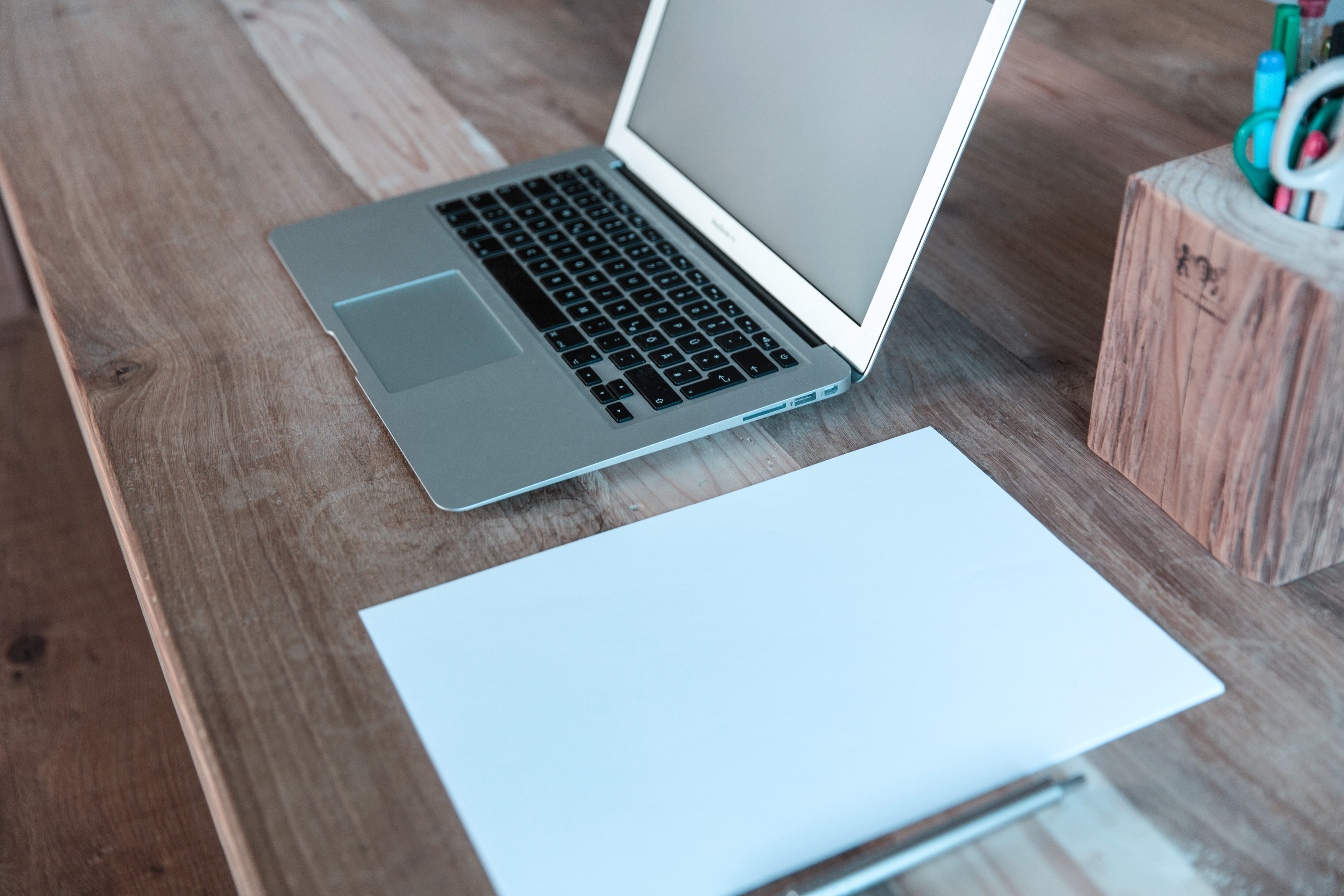 A sheet of white paper next to a MacBook on a wooden desk