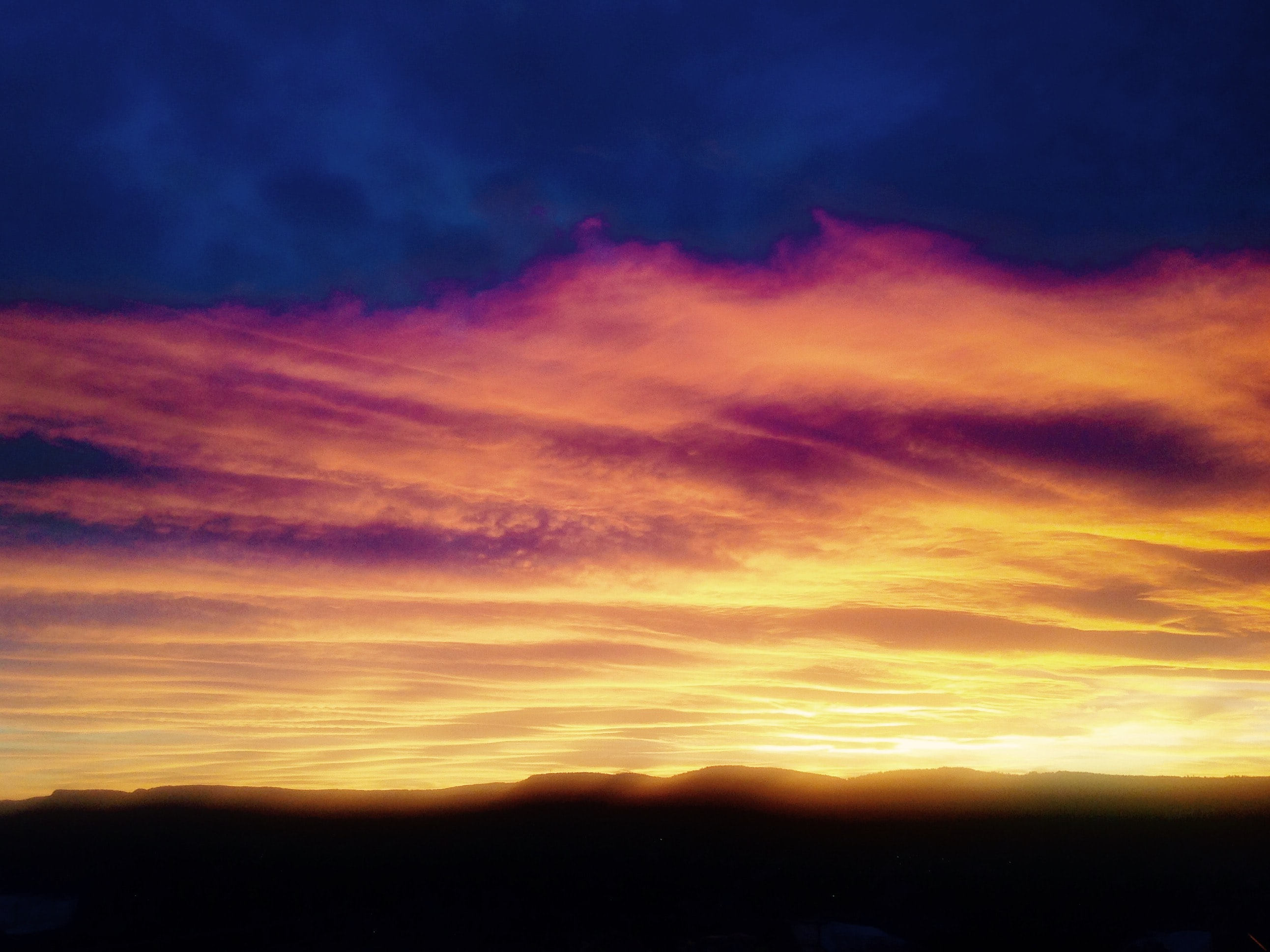 A dramatic sunrise or sunset with pink, blue, and orange tones in the clouds in Oslo