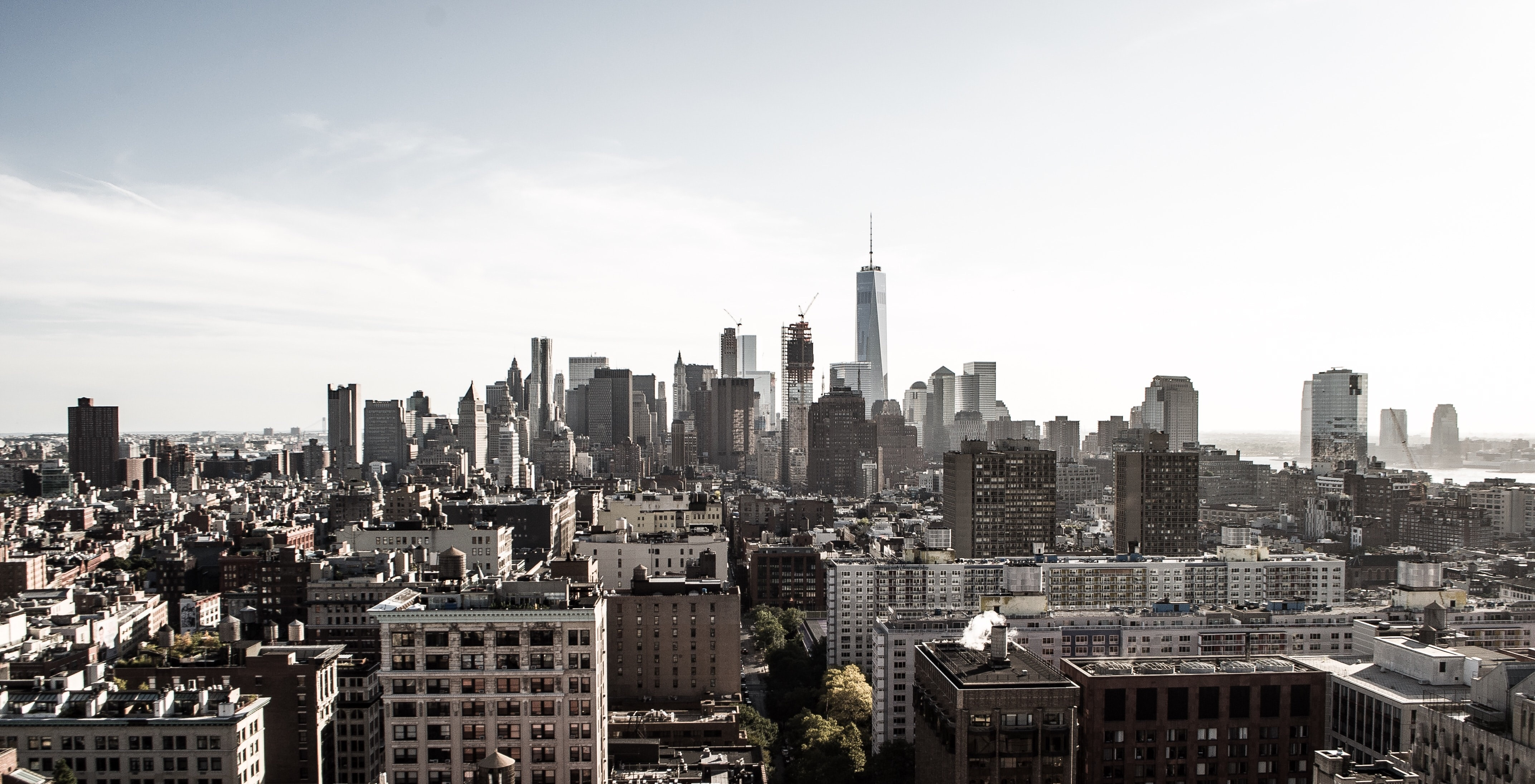 New York City's Financial District skyline from a distance against white cloudy skies