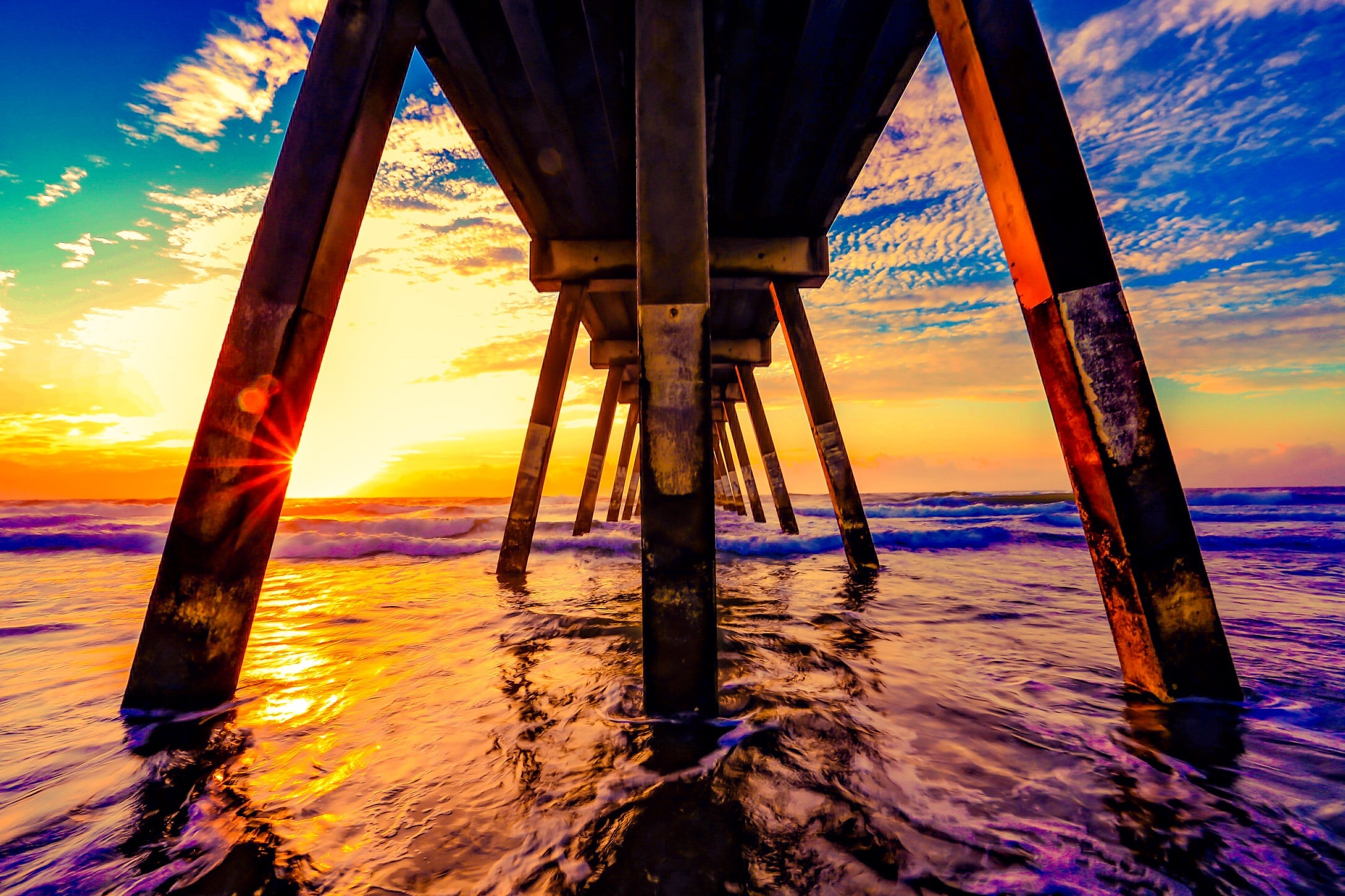 under view of brown wooden boardwalk during sunrise