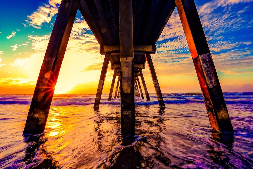 under view of brown wooden boardwalk during sunrise