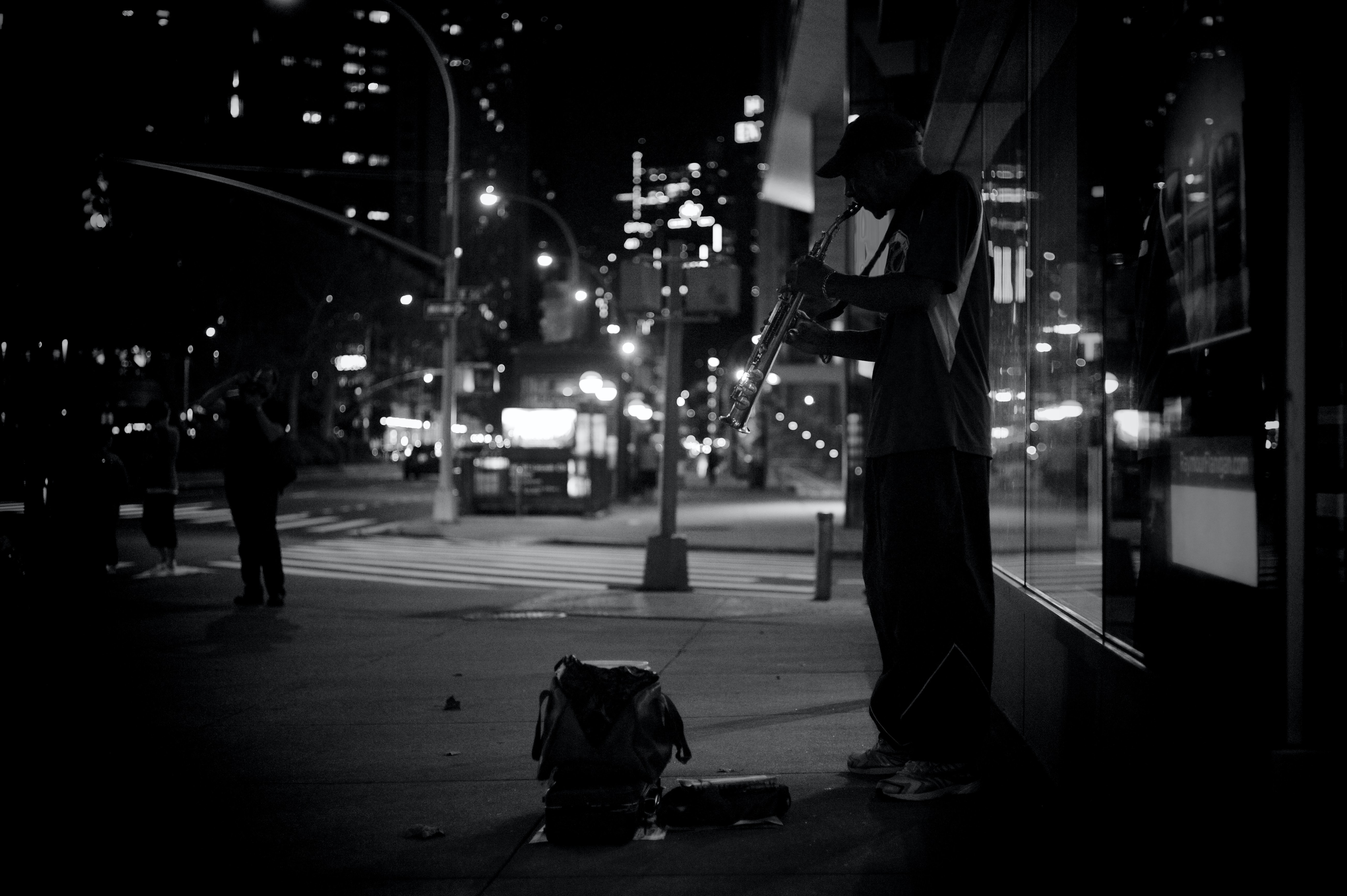 grayscale photography of man playing musical instrument beside road