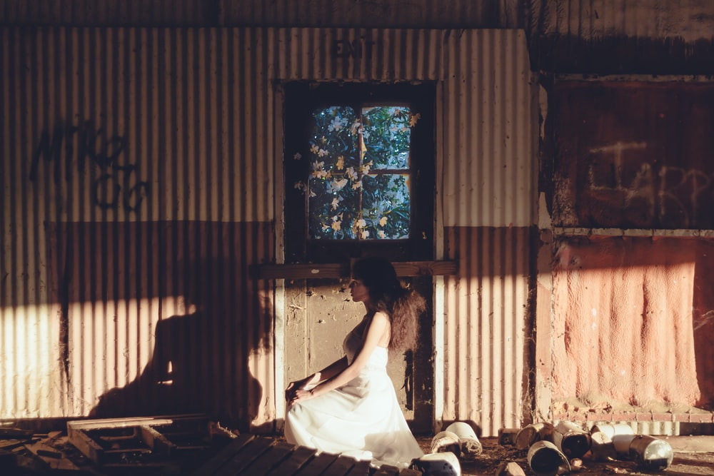 woman sitting near brown door