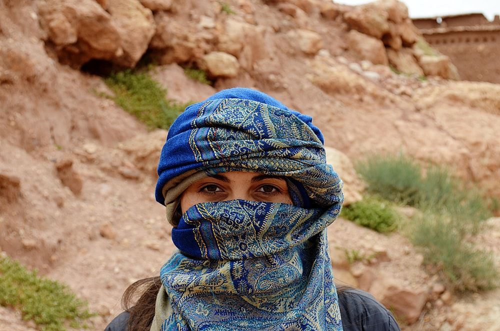 masked woman standing beside rock