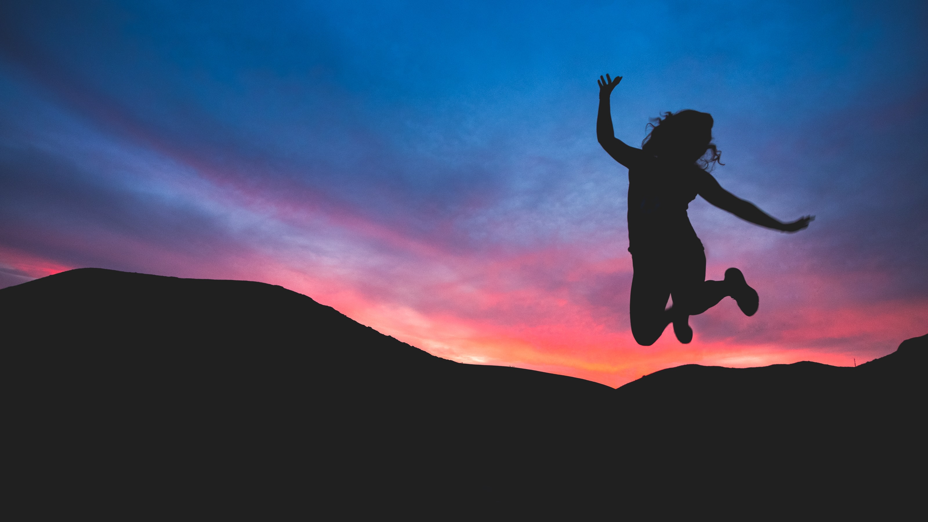 A woman in silhouette jumps for joy against dark mountains and a pink and purple sunset.
