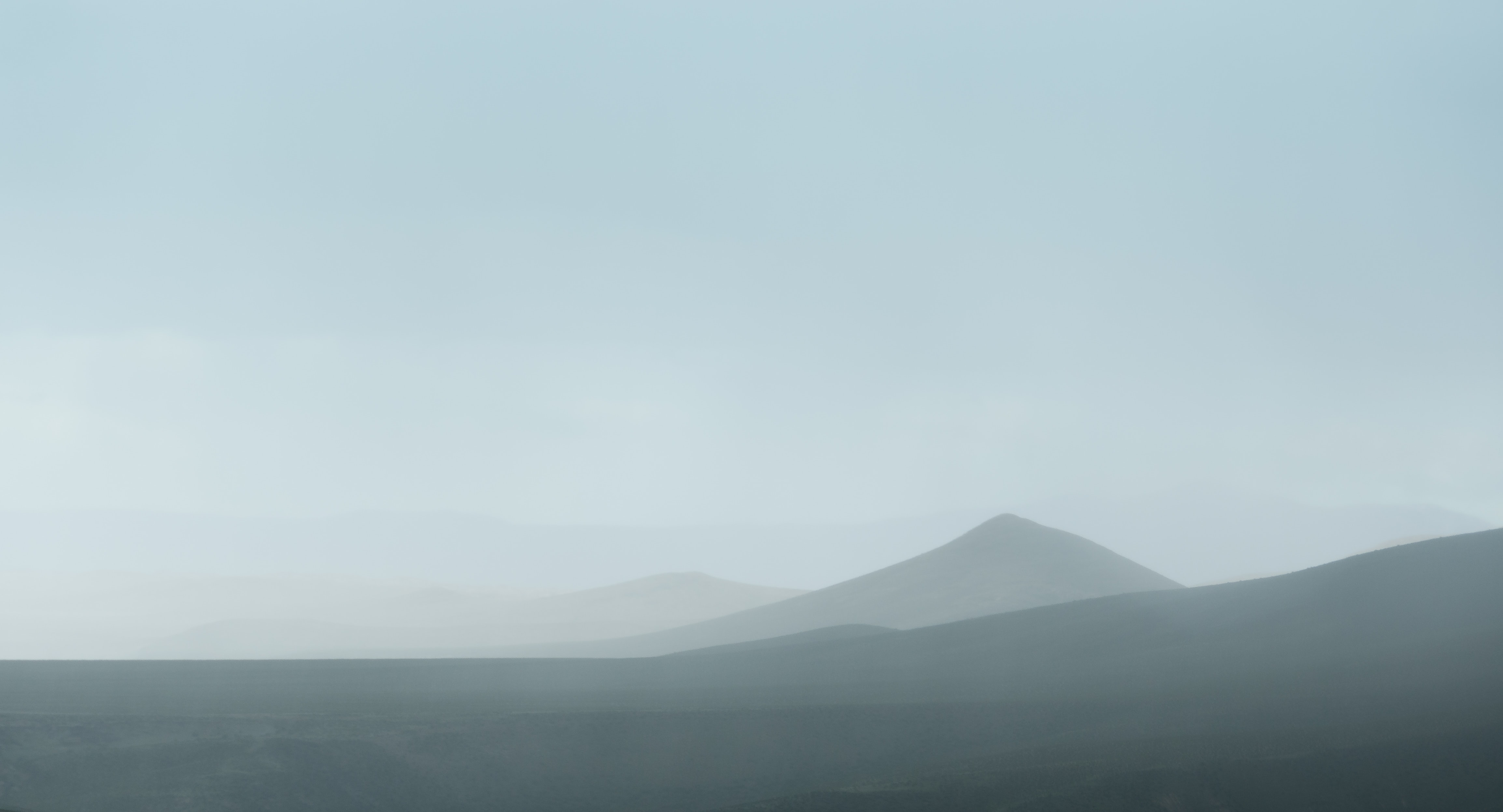 Fuzzy silhouettes of steep hills in a mist