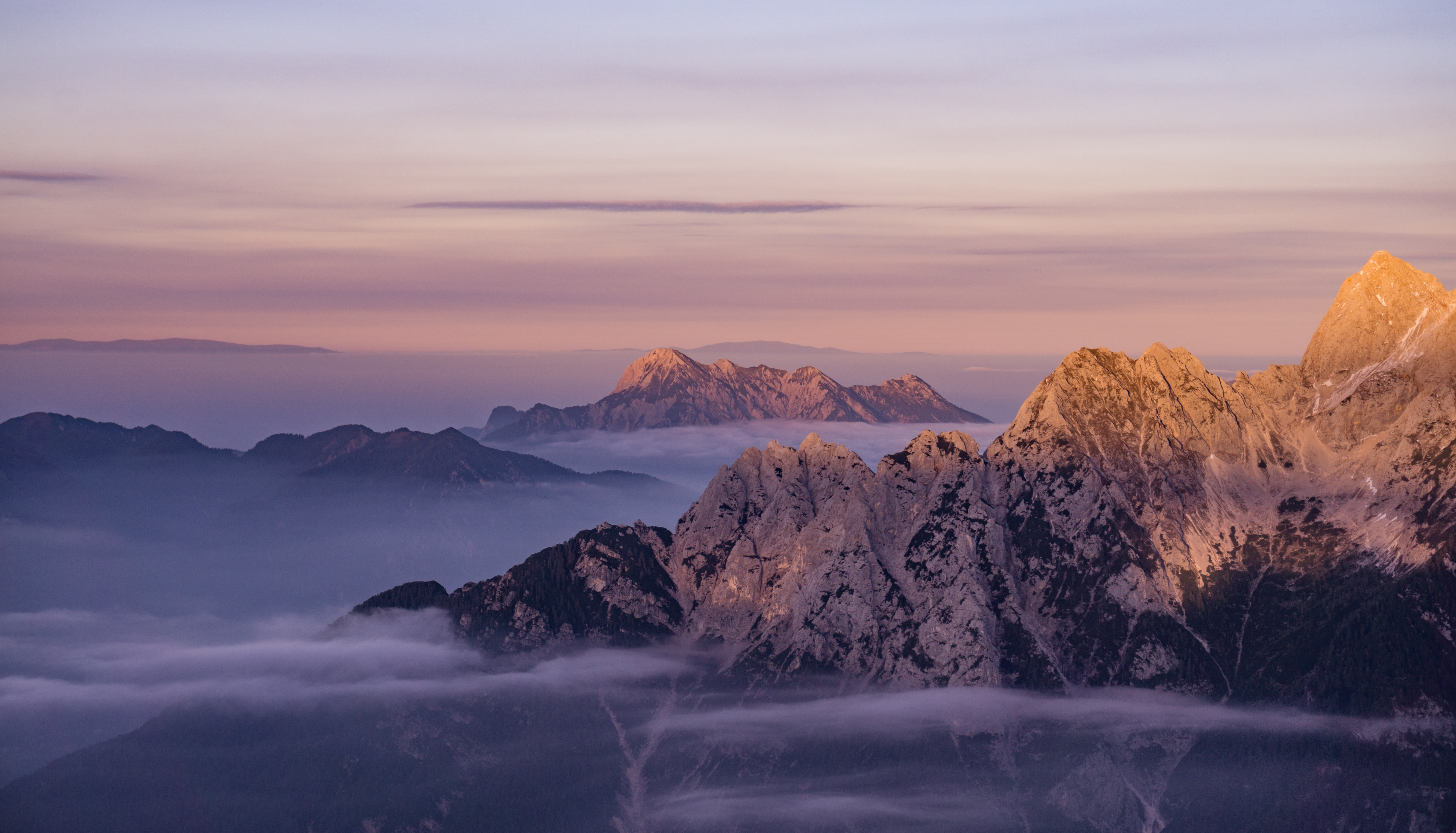 Wisps of fog surround rocky mountain summits
