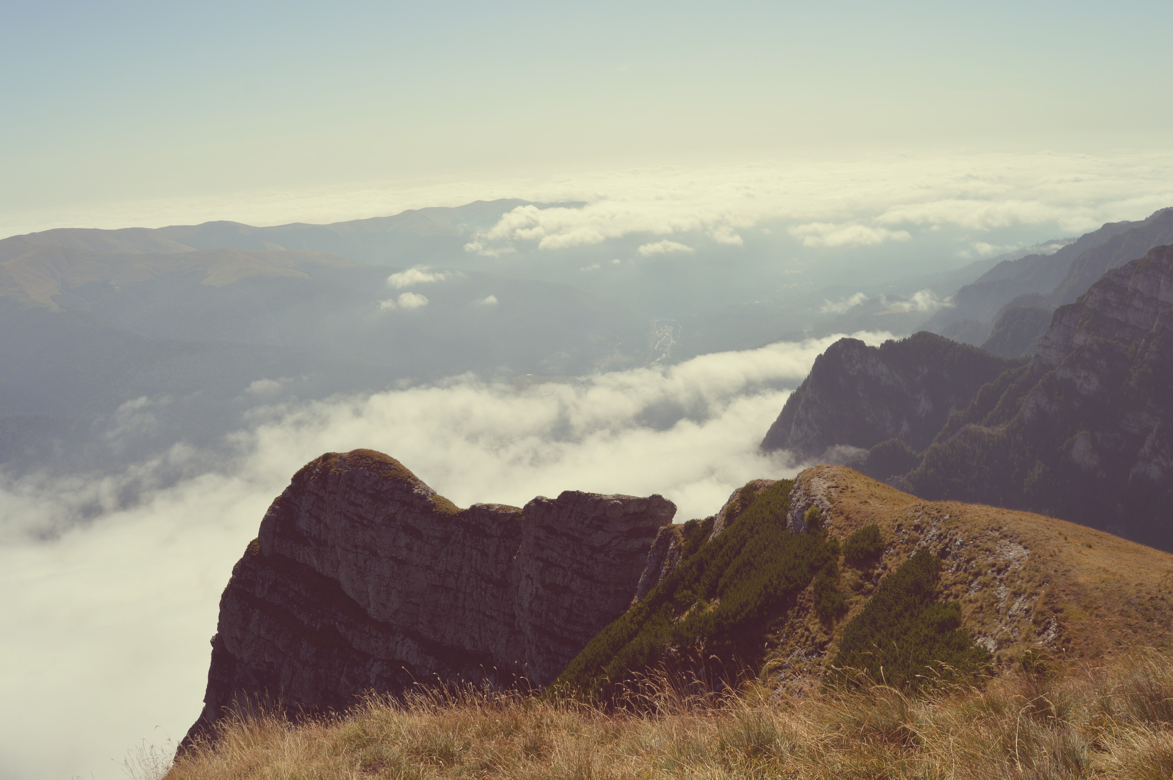 View from a mountain's crest on the clouds over a valley in Bucegi Mountains