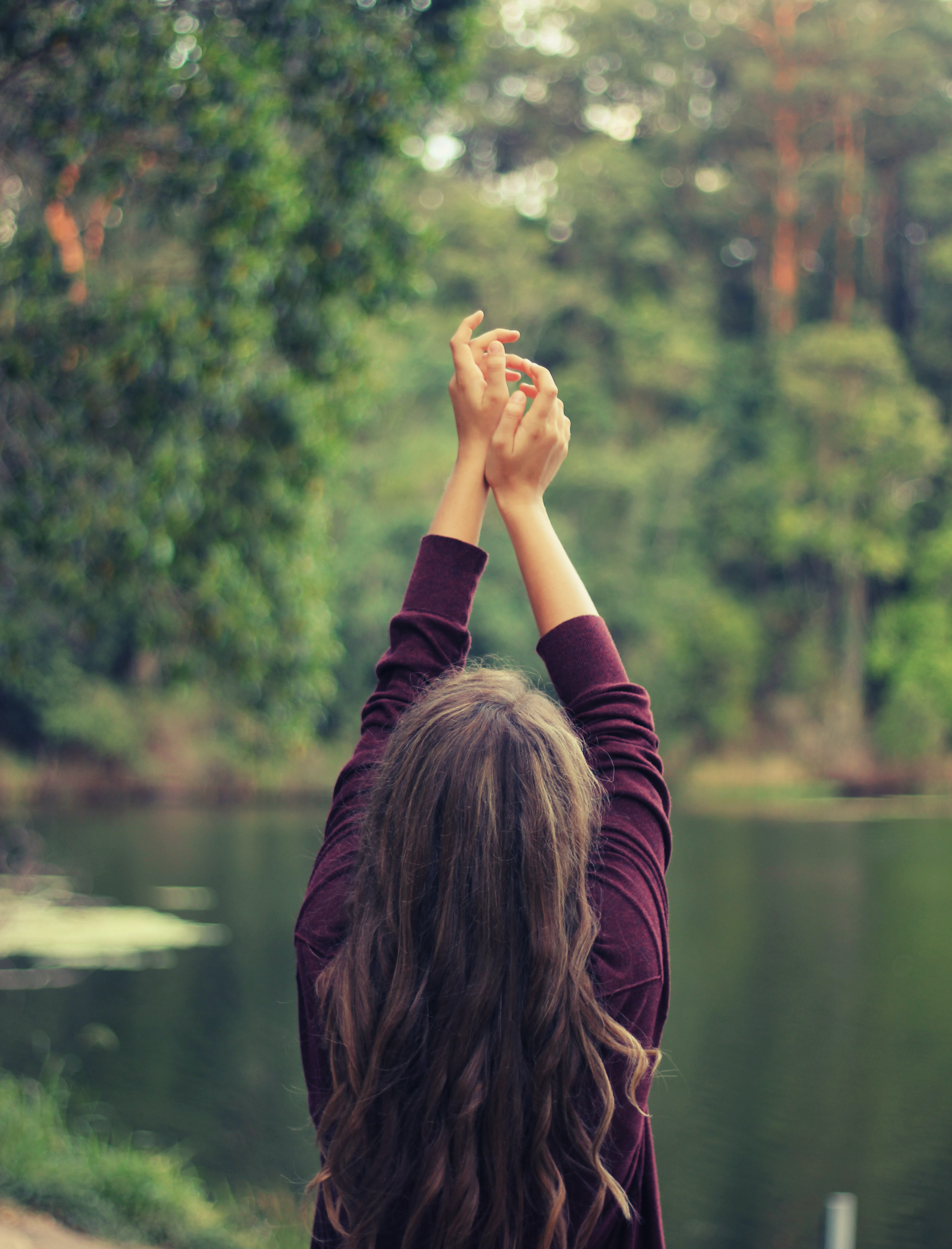 A woman in a purple sweater holds her arms in the air outdoors aside a lake