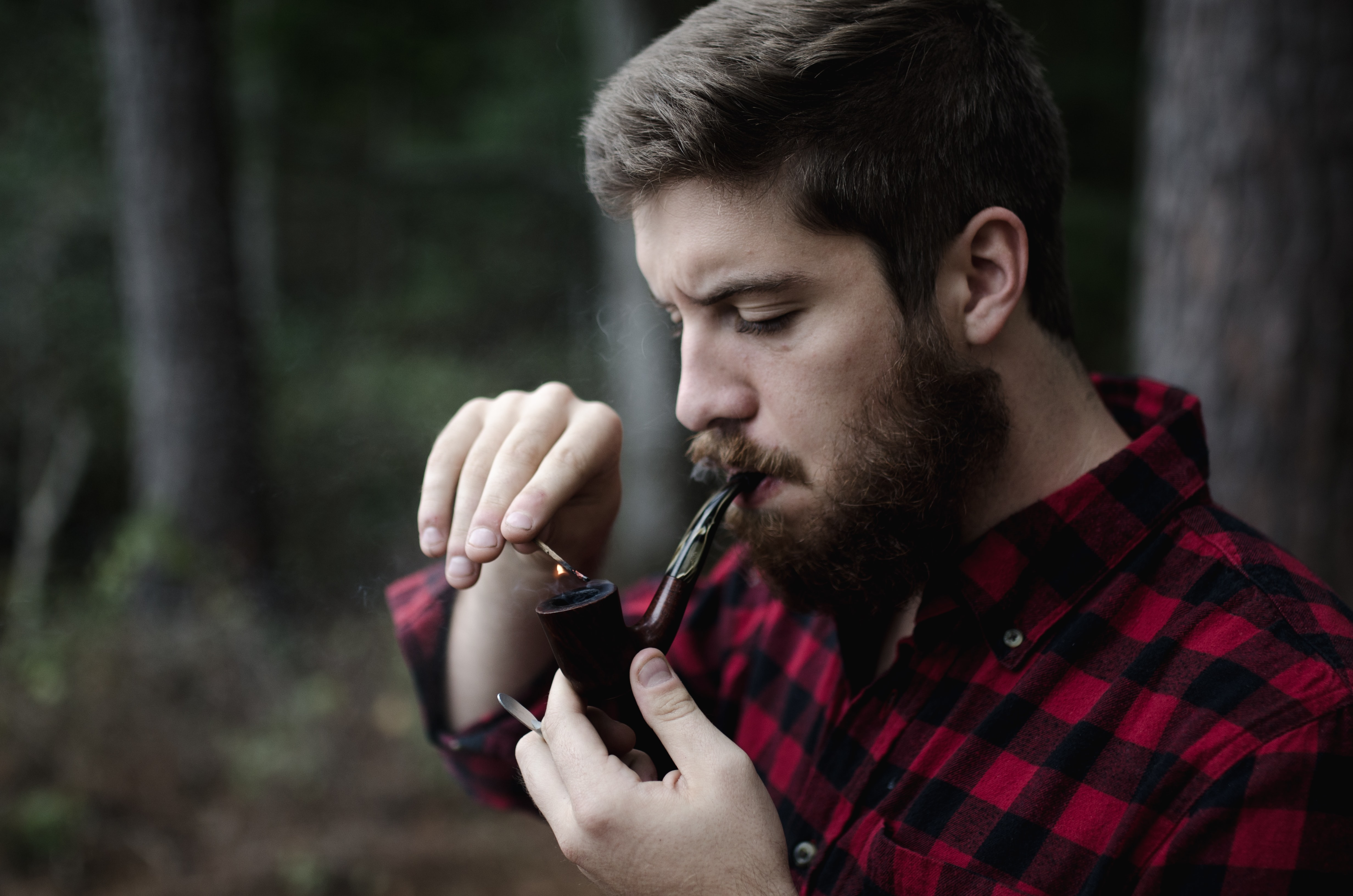 Hipster man in flannel with a beard lighting a pipe
