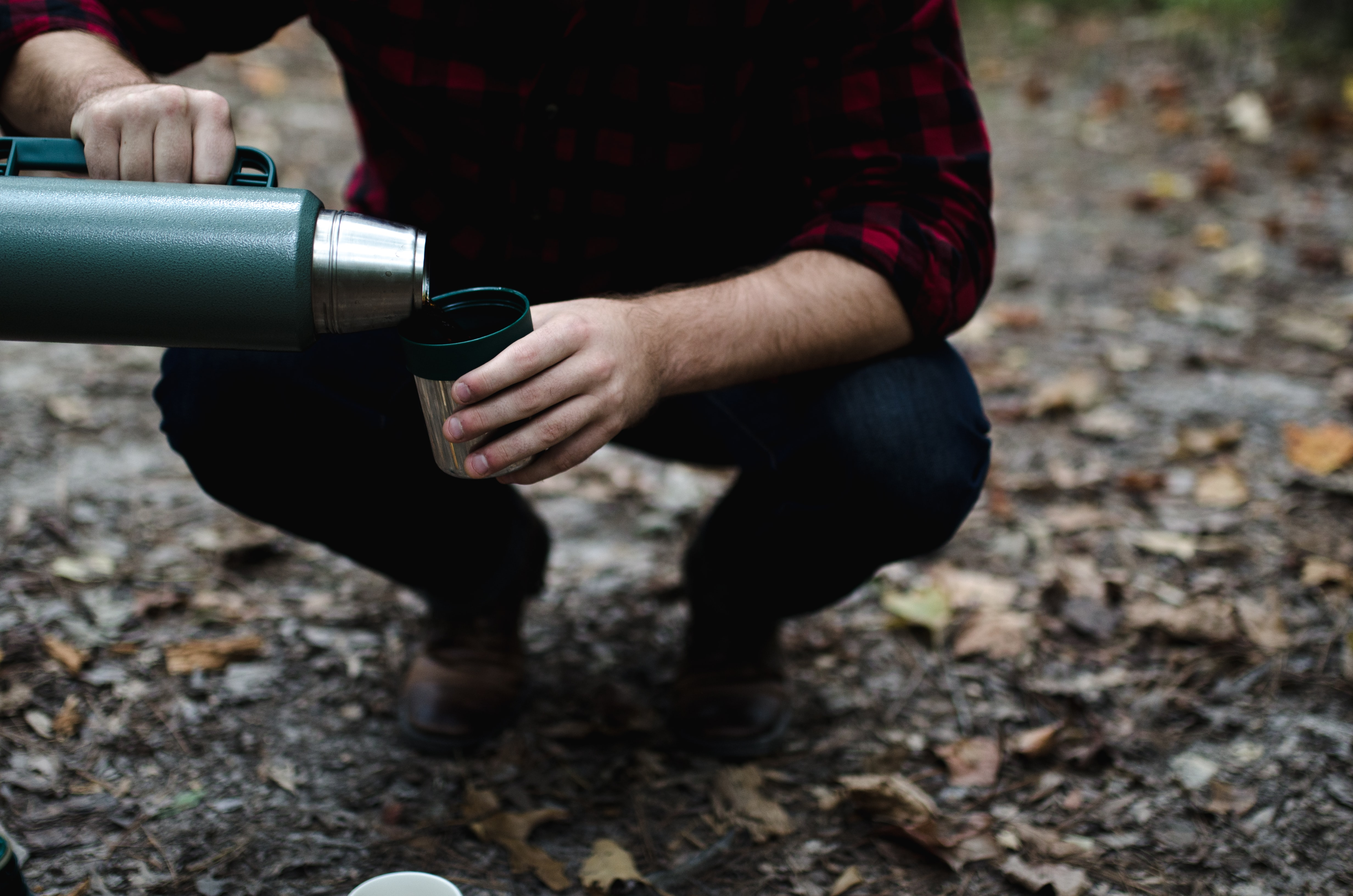 A man in plaid kneeling down and pouring drink from thermos into cap