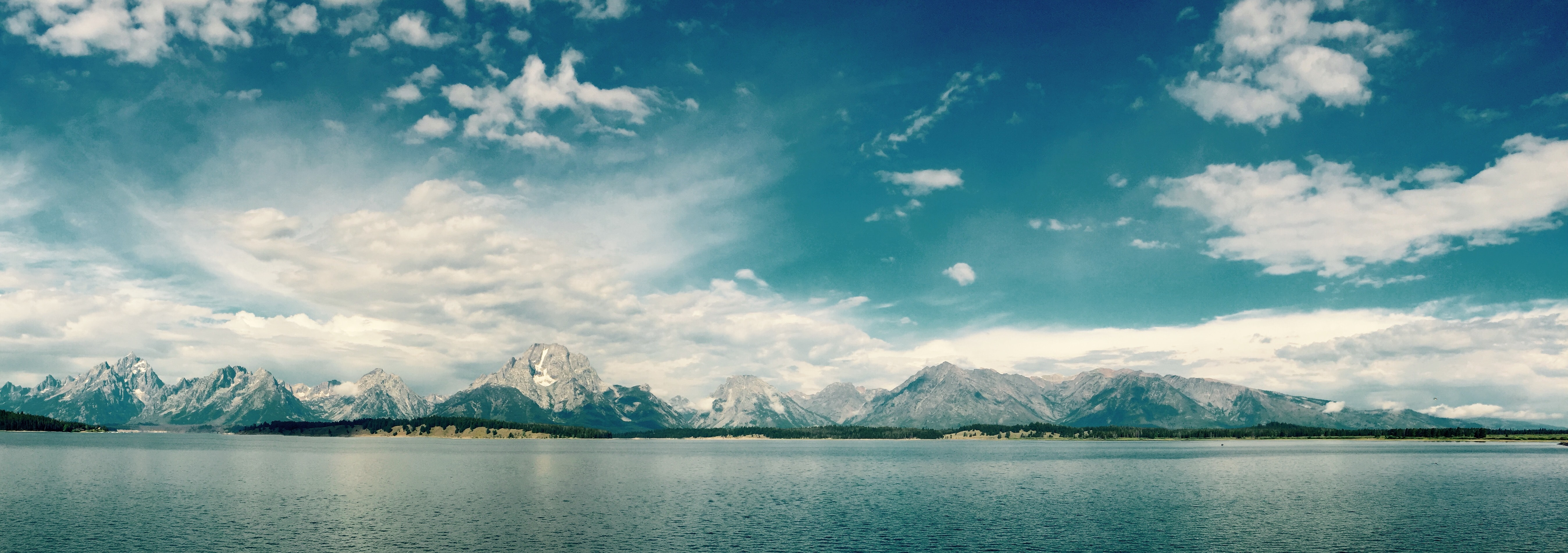 A panorama of a lake with mountains crowning the horizon in Grand Teton National Park