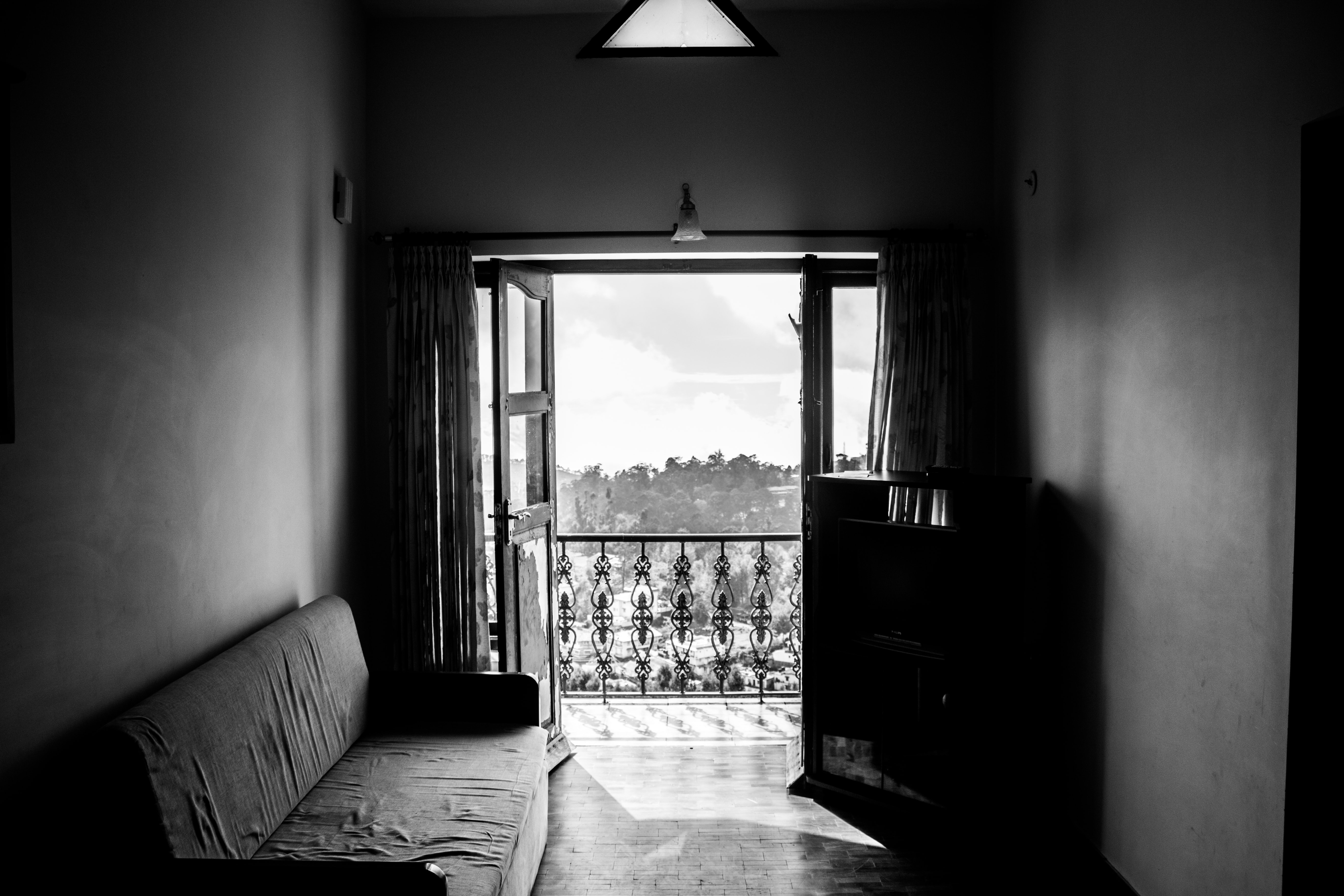 Black and white shot of worn down sofa and balcony window with view from flat, Kodaikanal