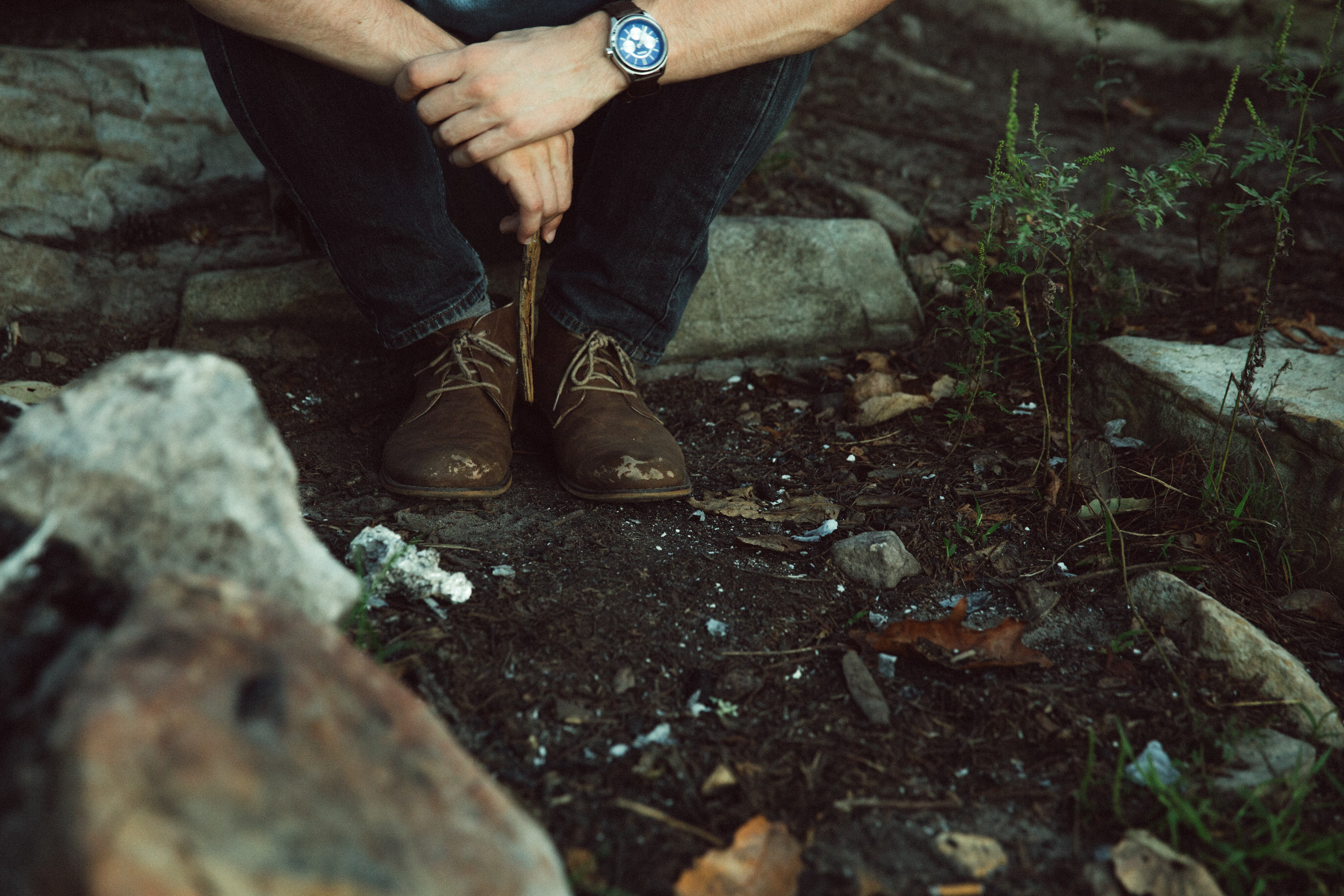 A low shot of a male hiker taking a rest on a rock in a forest in Chilhowee