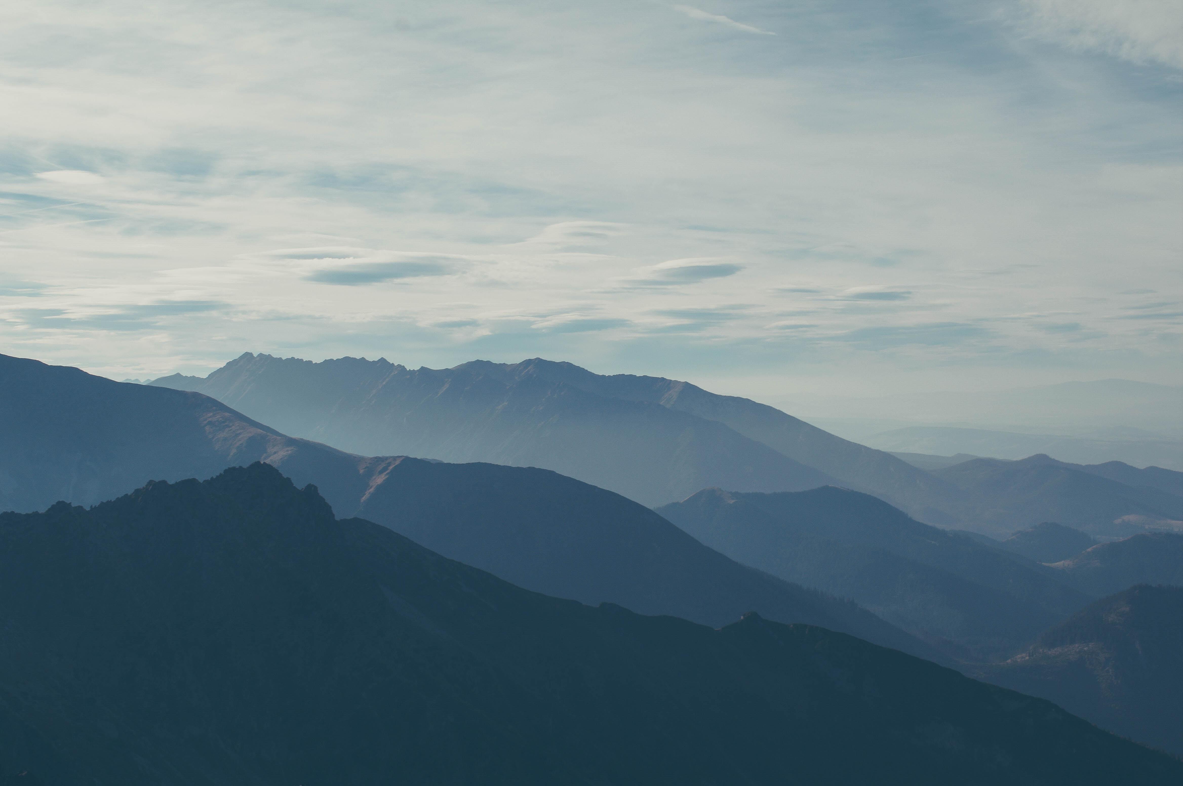 A hazy shot of several mountain ridges stretching to the horizon