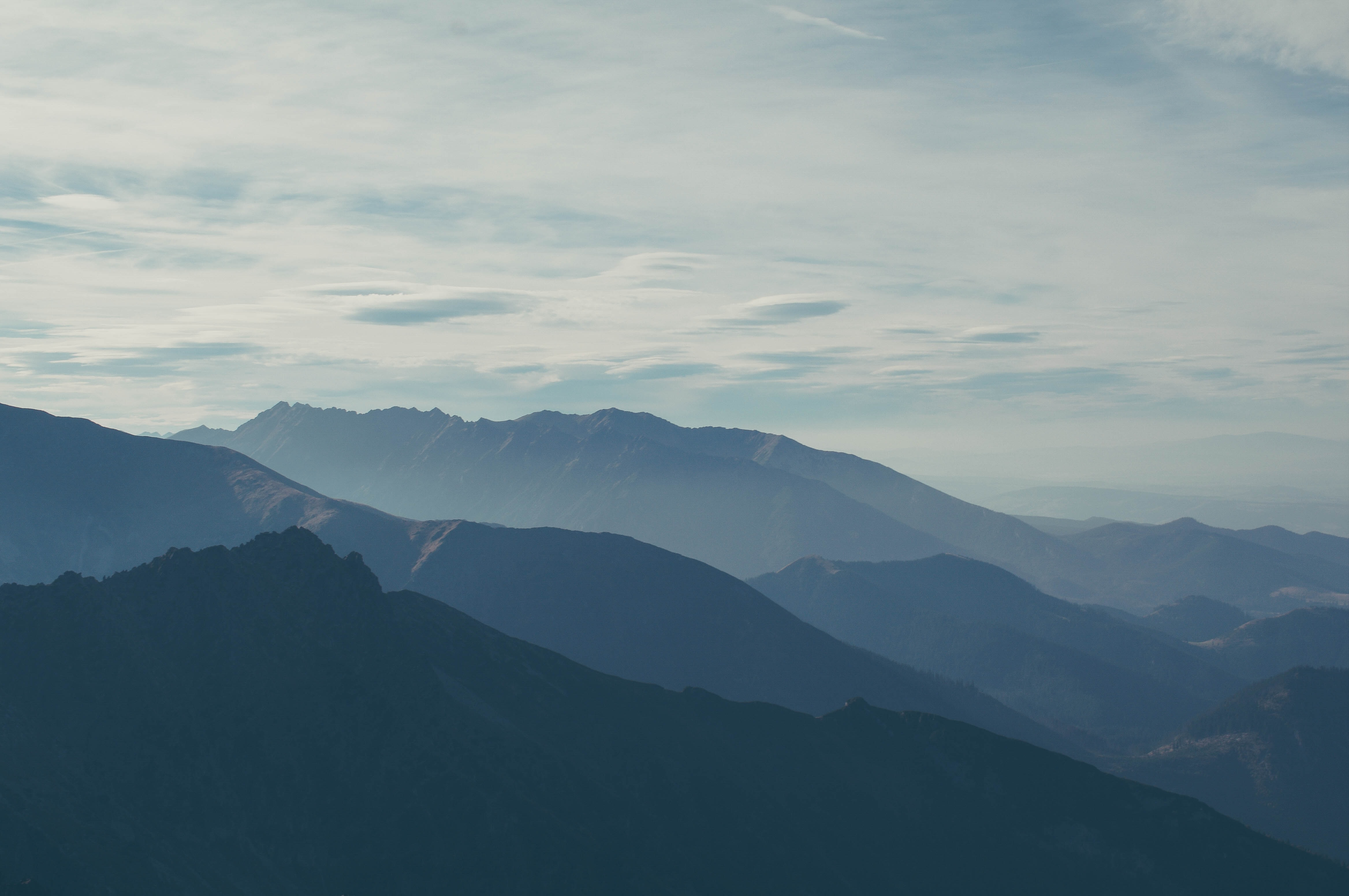 A hazy shot of several mountain ridges stretching to the horizon