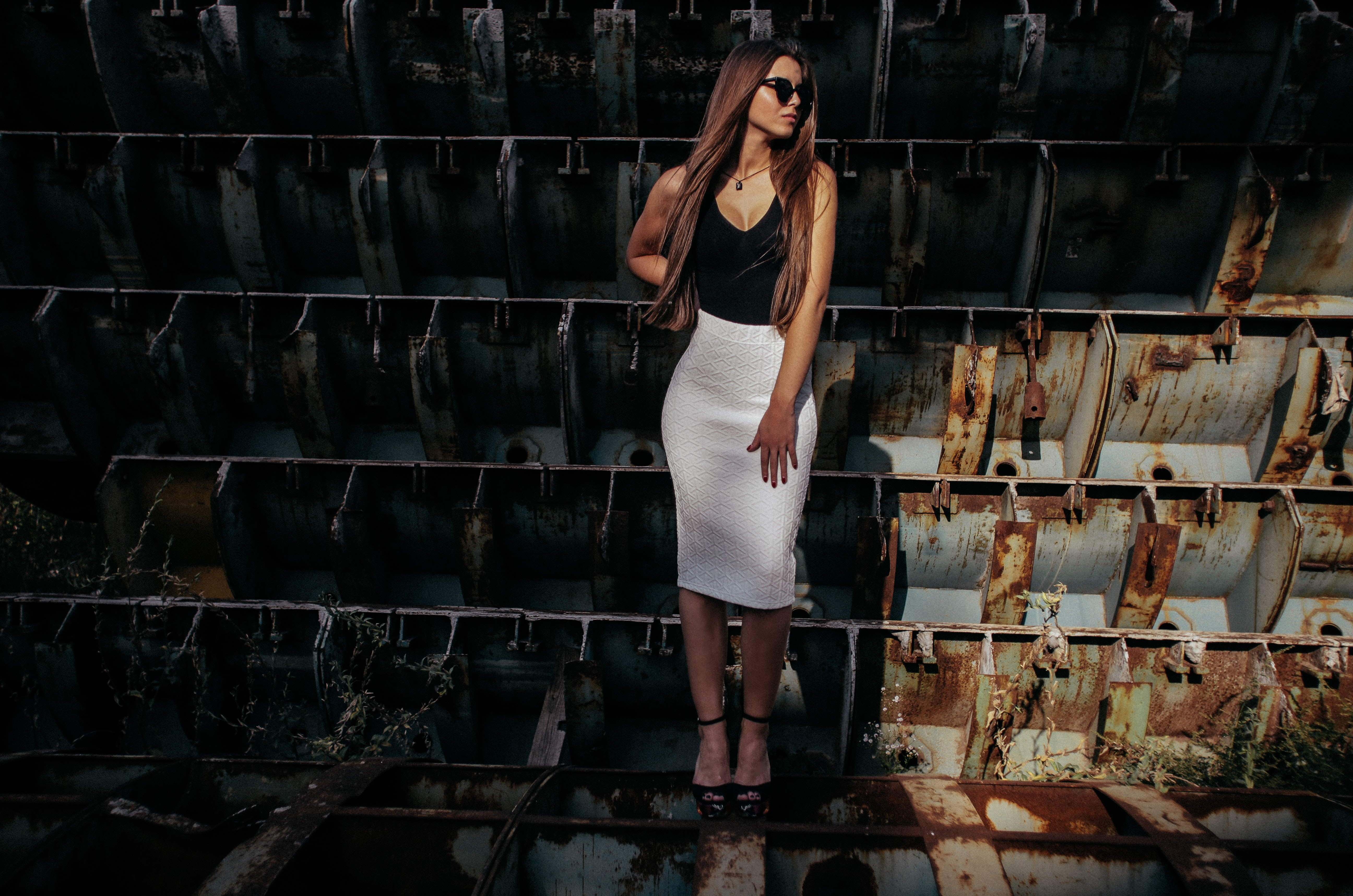 woman in black and white sleeveless dress on gray and brown steel frames