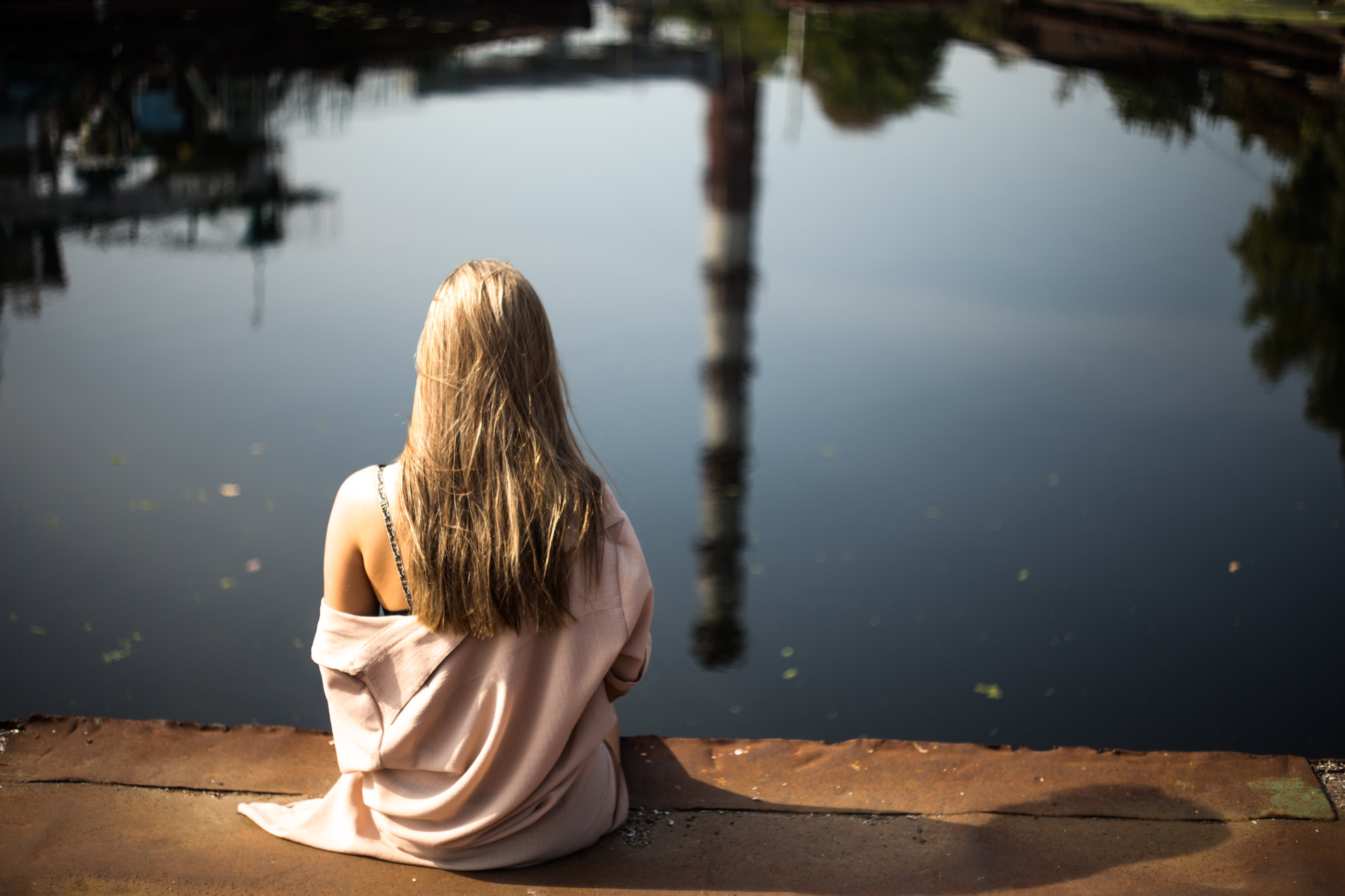 woman sitting down on porch beside body of water
