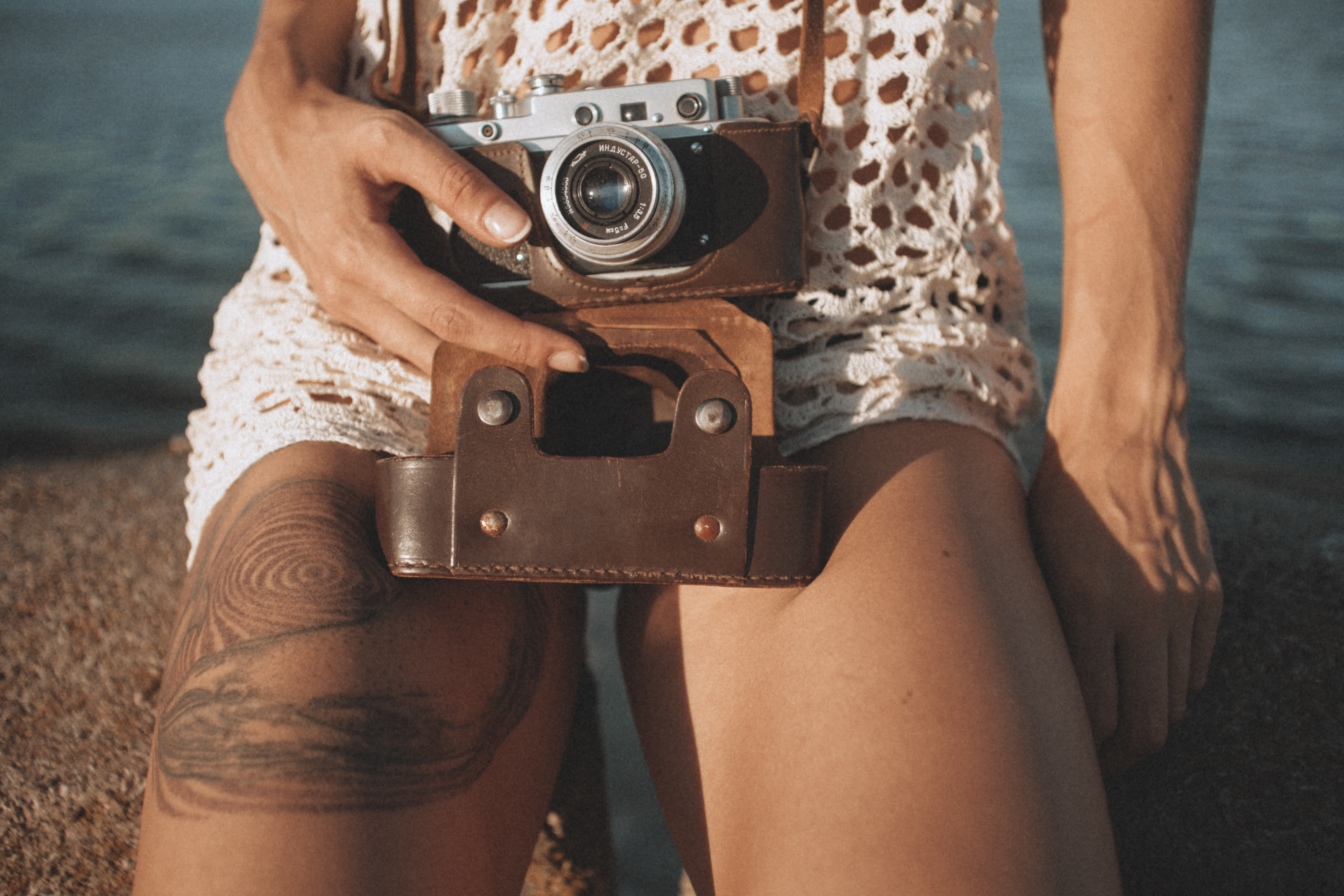 Woman with whale tattoo on her thigh holding a vintage camera and sitting by the water