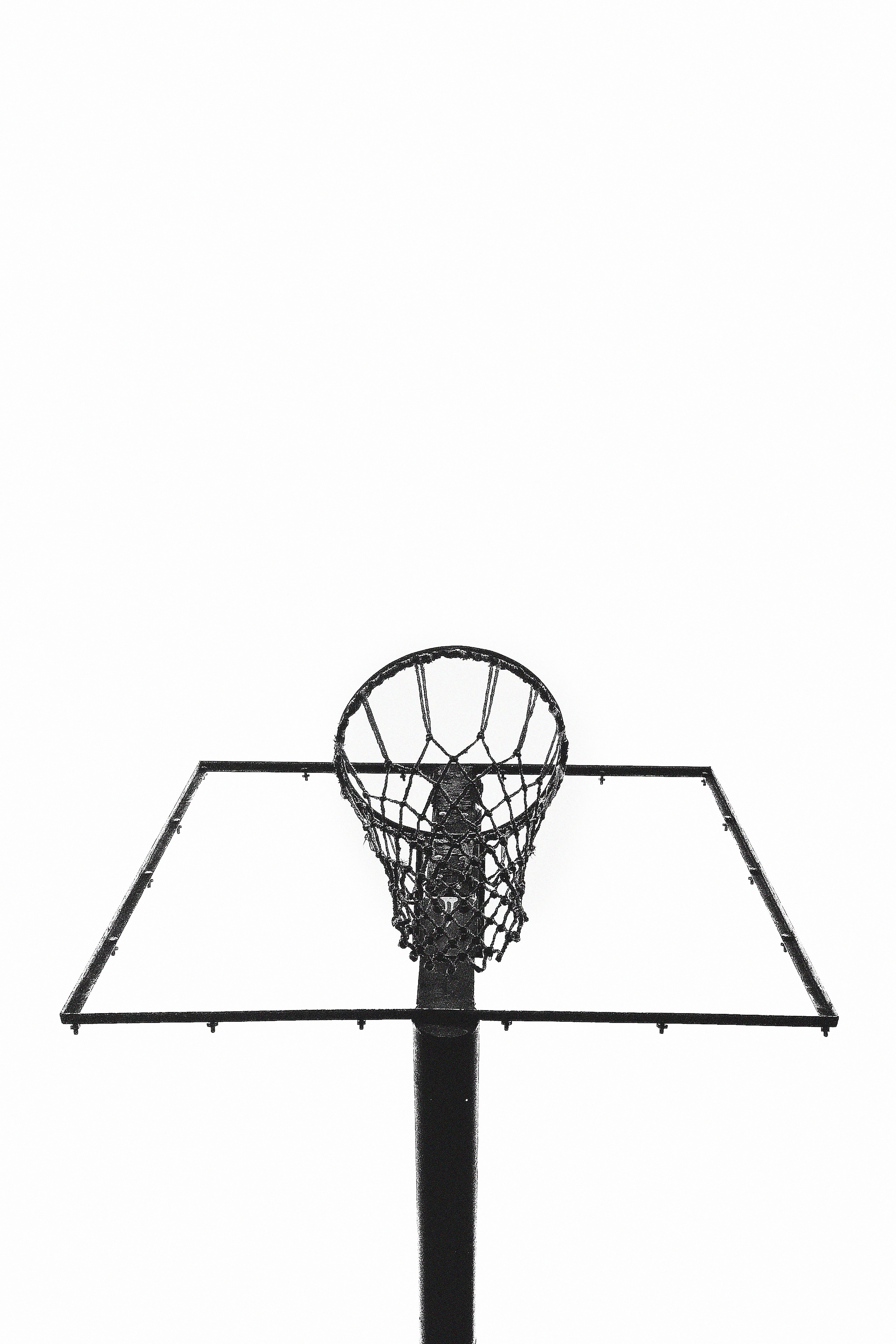 Staring up at a basketball net hoop outside, with complete whiteness in the background.